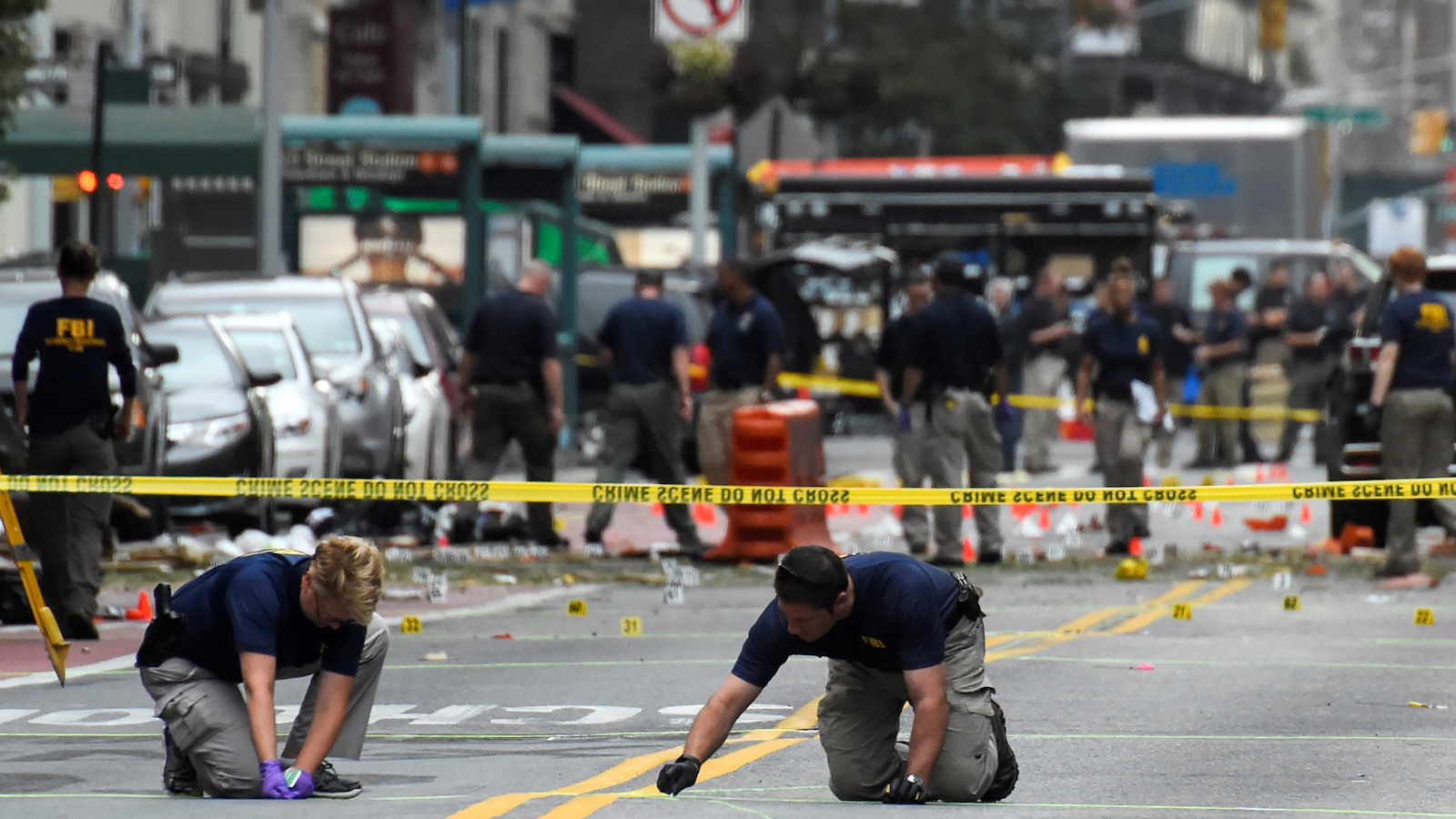 Federal Bureau of Investigation (FBI) officials mark the ground near the site of an explosion in the Chelsea neighborhood of Manhattan, New York, U.S.  September 18, 2016.  REUTERS/Rashid Umar Abbasi     TPX IMAGES OF THE DAY      - RTSO9XA