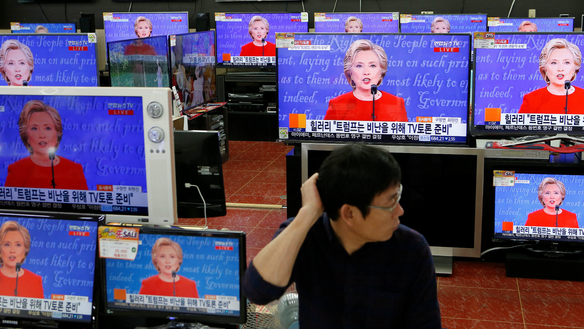 A sales assistant watches the TV broadcast of the first presidential debate between U.S. Democratic presidential candidate Hillary Clinton and Republican presidential nominee Donald Trump, in Seoul, South Korea, September 27, 2016.