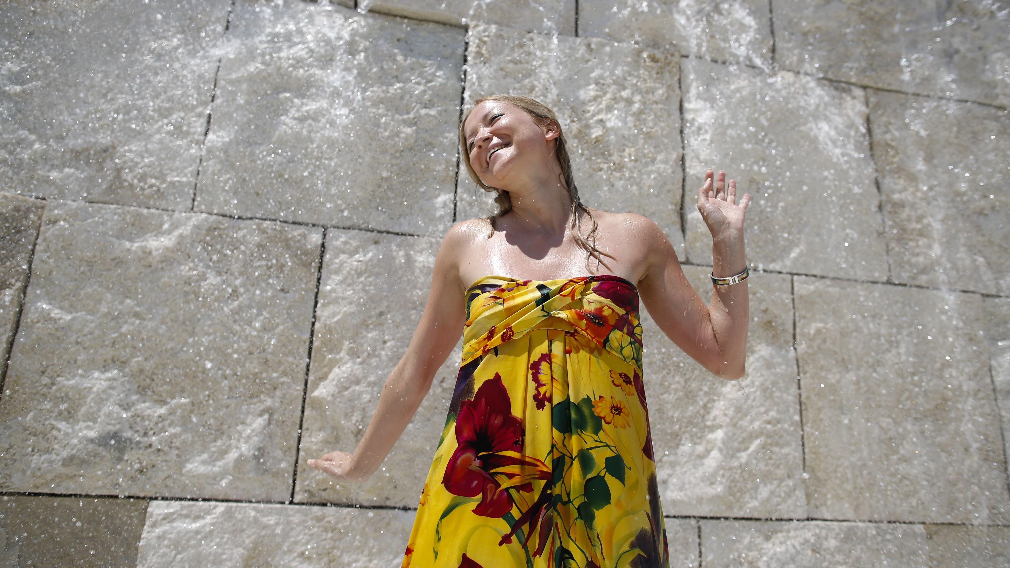 A woman cools down at a fountain on a hot summer day in downtown Rome July 27, 2013.