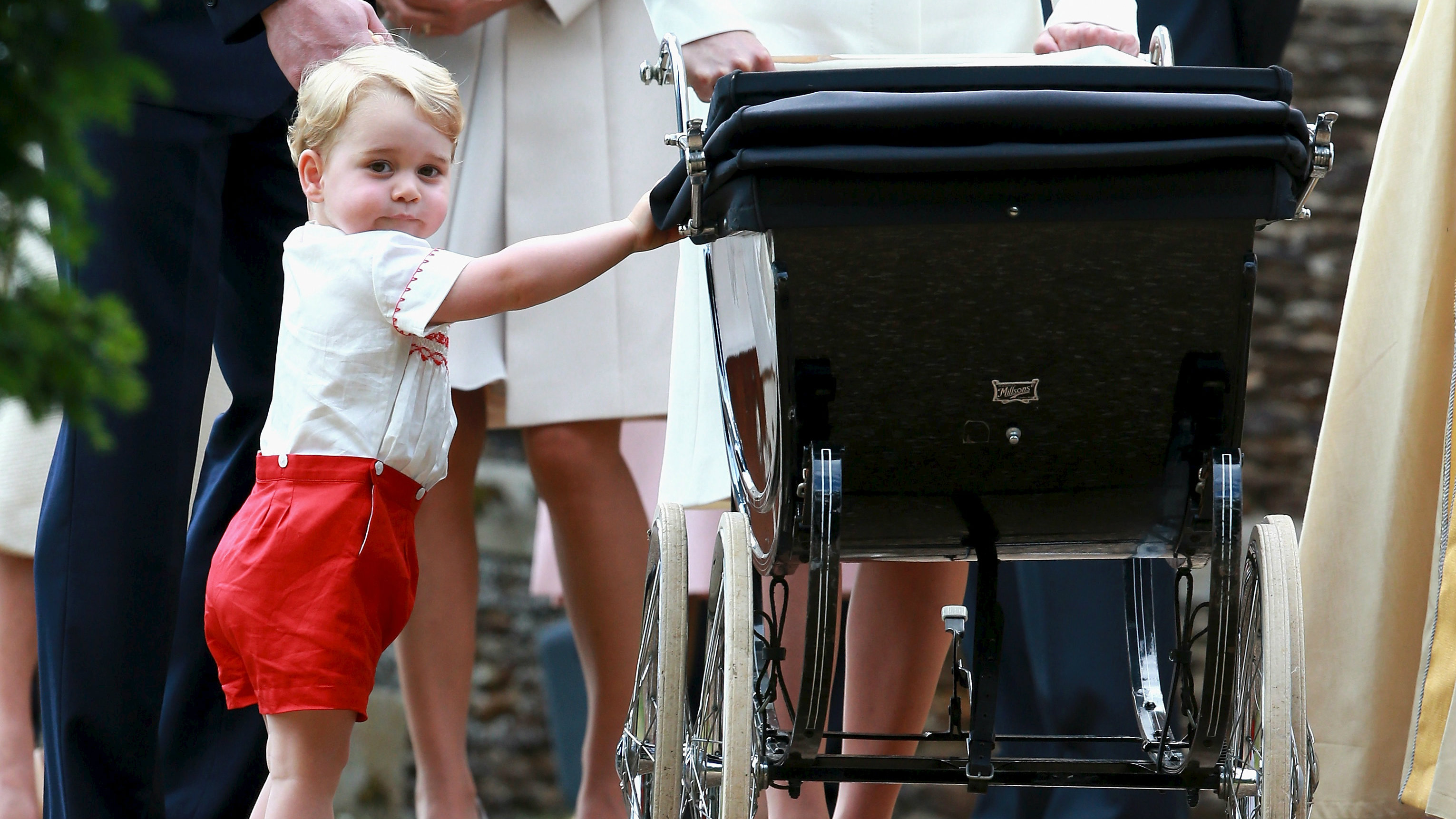 Britain's Prince George looks at his sister Princess Charlotte in her pram as he leaves after her christening.