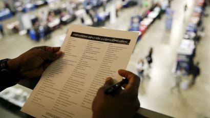 A person looks at a list of employers attending a job fair.
