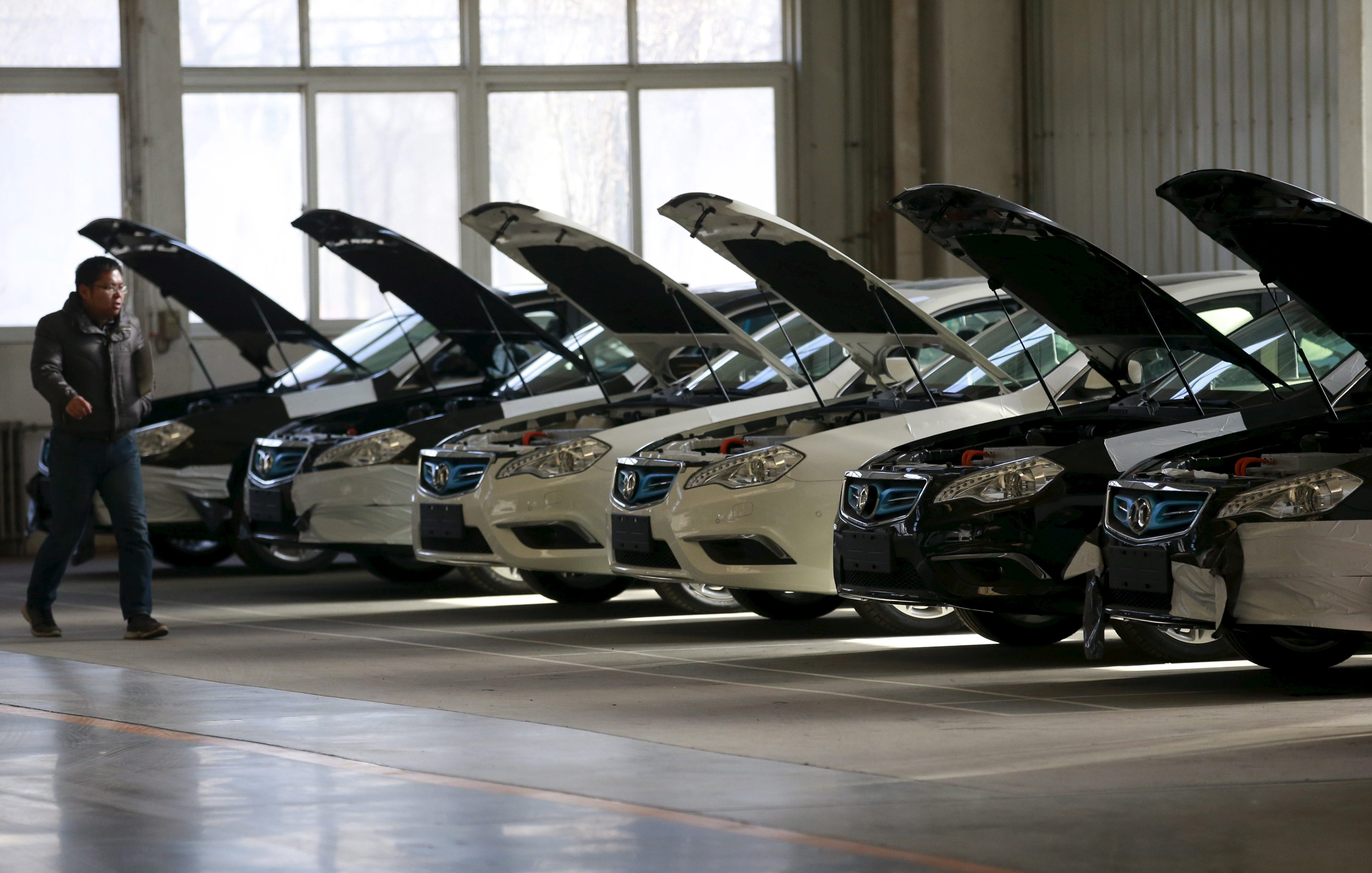 A man walks past cars at an assembly line producing electronic cars at a factory of Beijing Electric Vehicle, funded by BAIC Group, in Beijing, China, January 18, 2016.REUTERS/Kim Kyung-Hoon - RTX22VIN