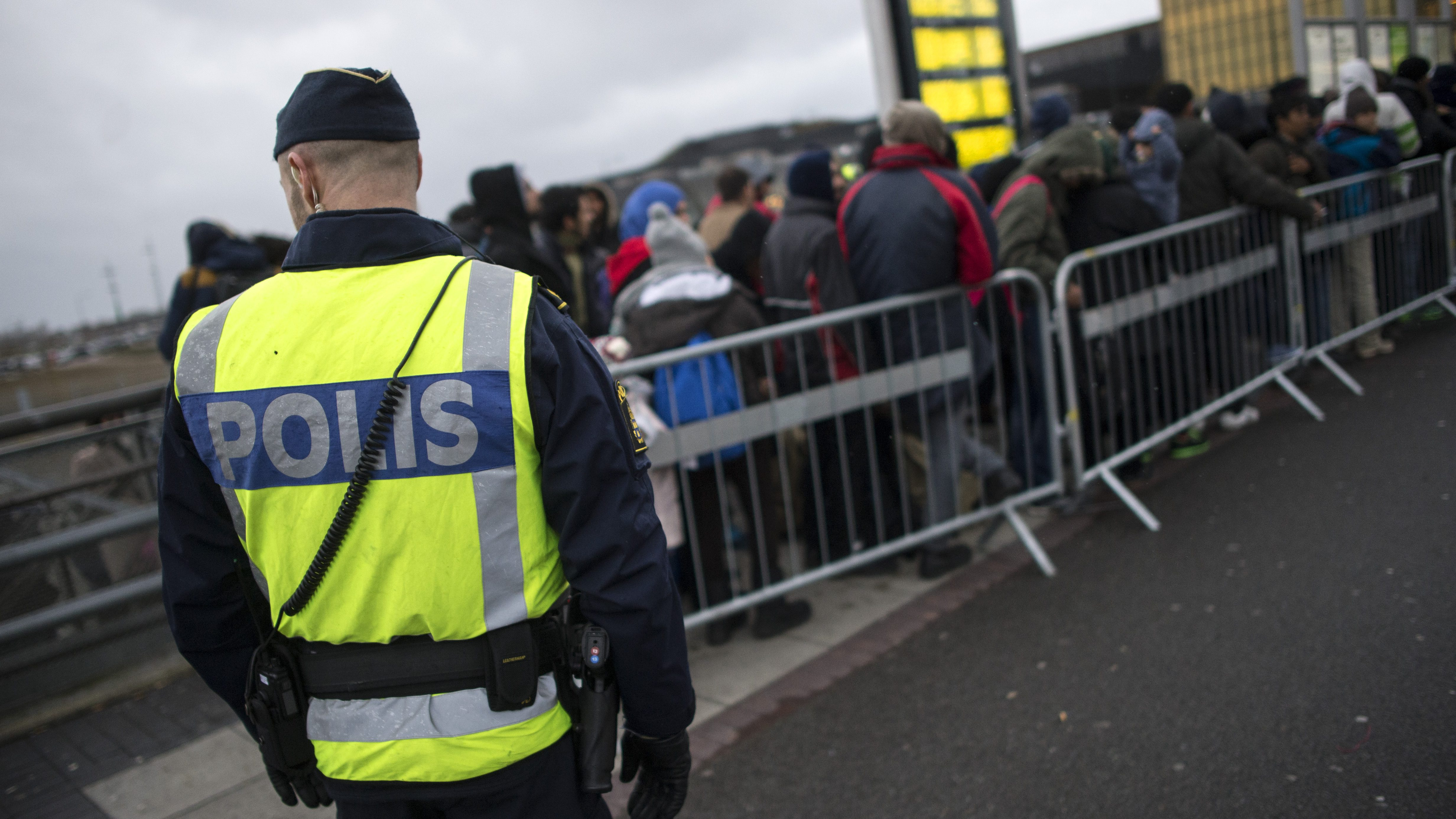A police officer keeps guard as migrants arrive at Hyllie station outside Malmo.