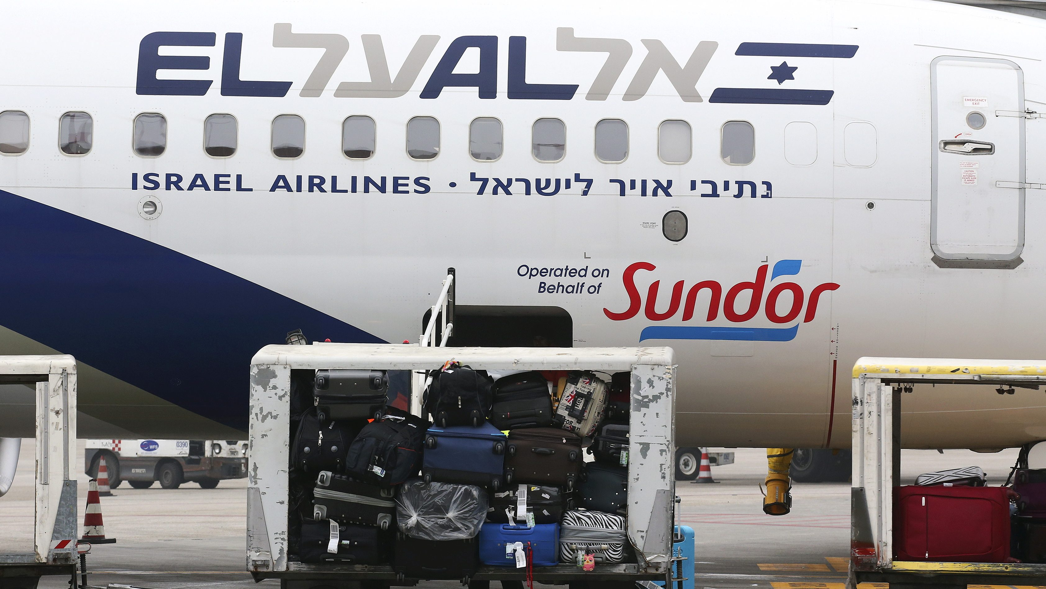 Baggage carts are seen on the tarmac near an El Al Israel Airlines plane at Venice airport February 1, 2016.  REUTERS/Alessandro Bianchi  - RTX24ZF8