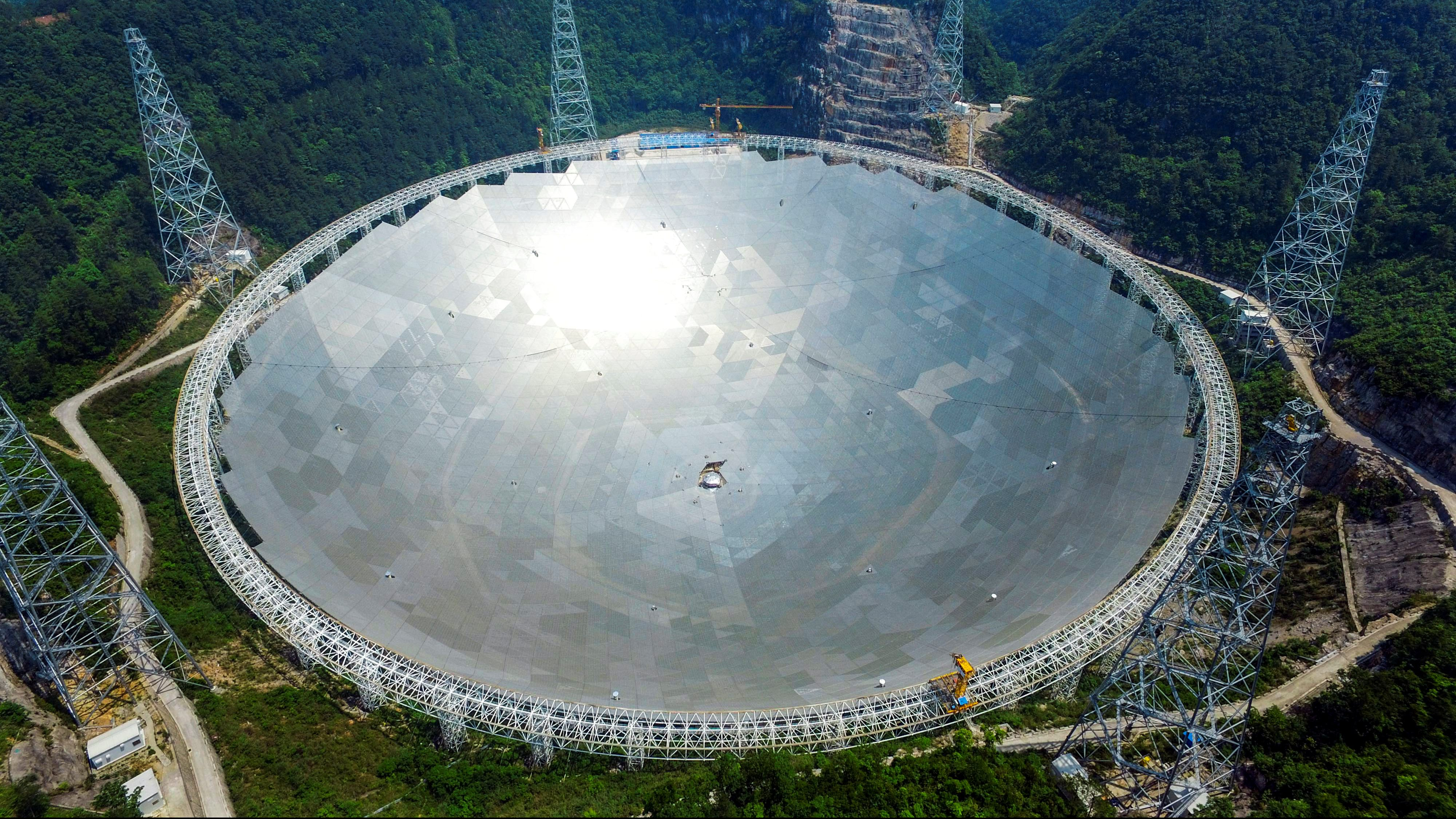 A 500-metre (1,640-ft.) aperture spherical telescope (FAST) is seen at the final stage of construction, among the mountains in Pingtang county, Guizhou province, China, May 7, 2016.