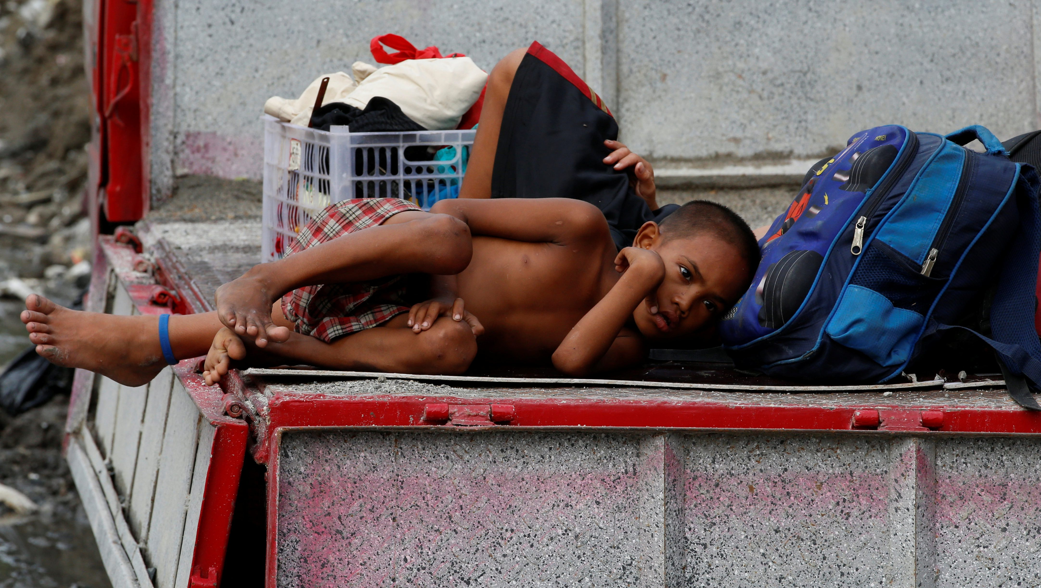 A resident lies on a truck with his belongings after around a dozen homeless people were evicted along a road in Makati, Metro Manila, Philippines August 18, 2016.  REUTERS/Erik De Castro - RTX2LPFE