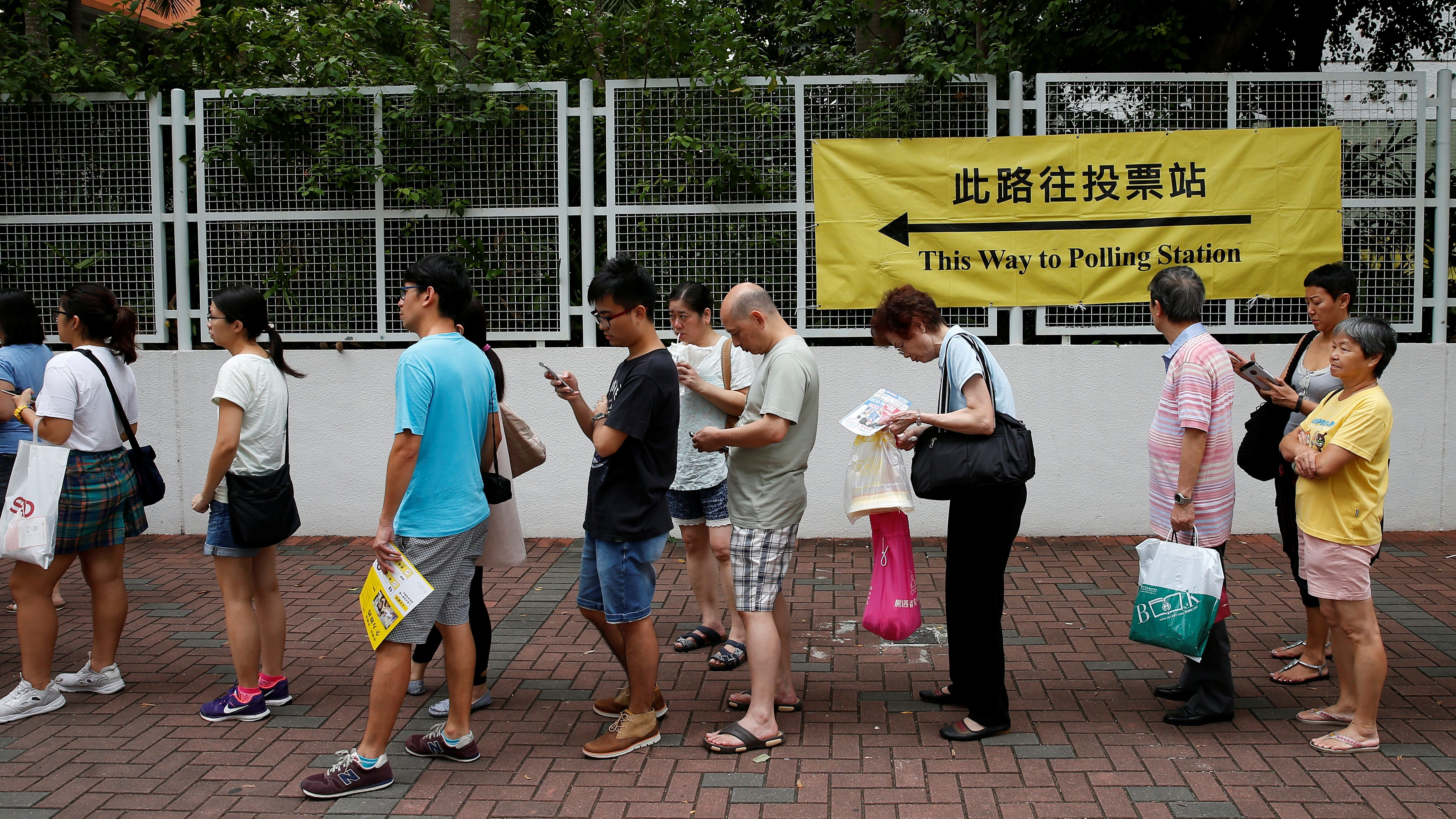 People queue as they wait to cast their votes for the Legislative Council election at a polling station in Hong Kong, China September 4, 2016. REUTERS/Tyrone Siu - RTX2O1DJ
