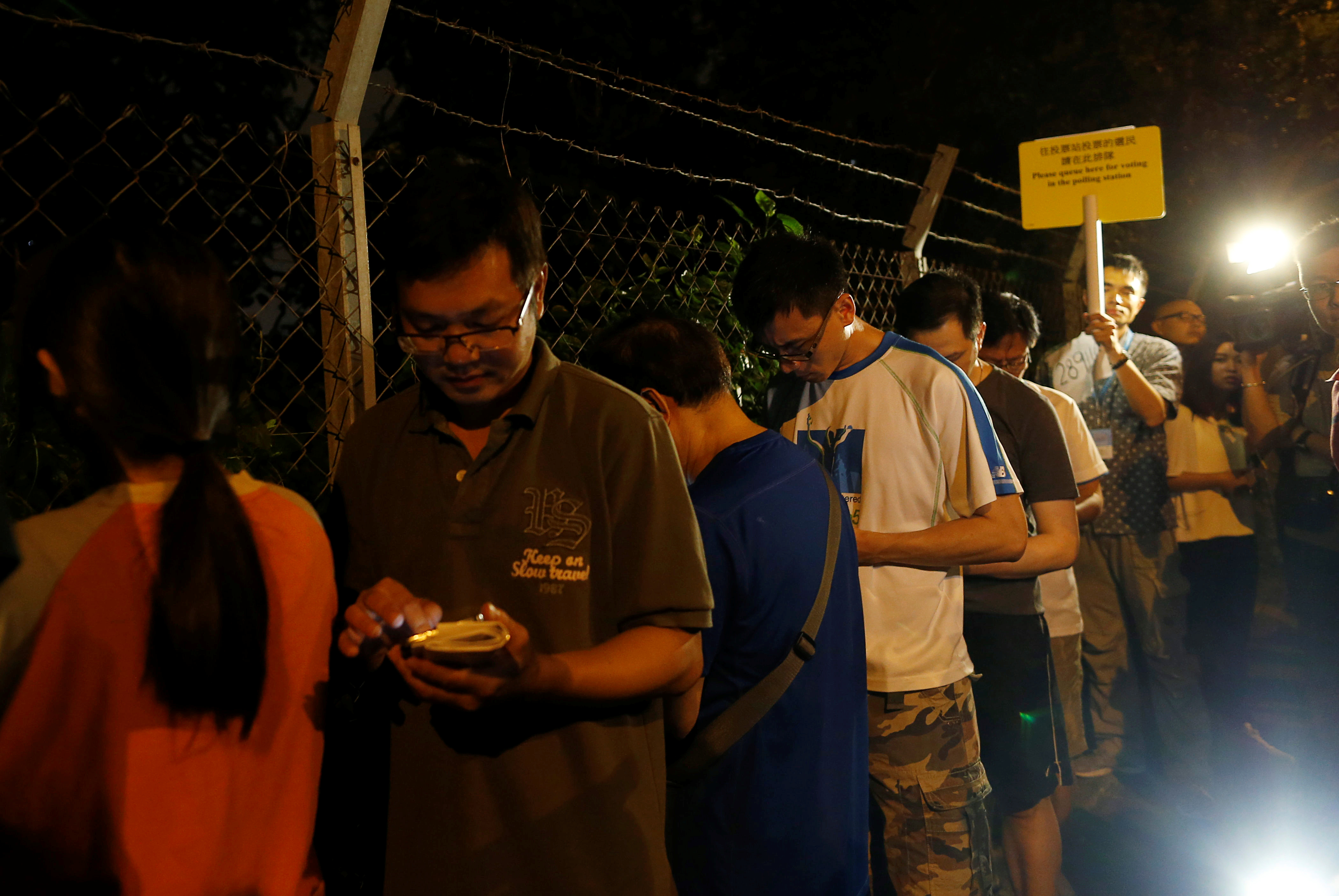 People queue as they wait to cast their votes at a polling station in Hong Kong, China