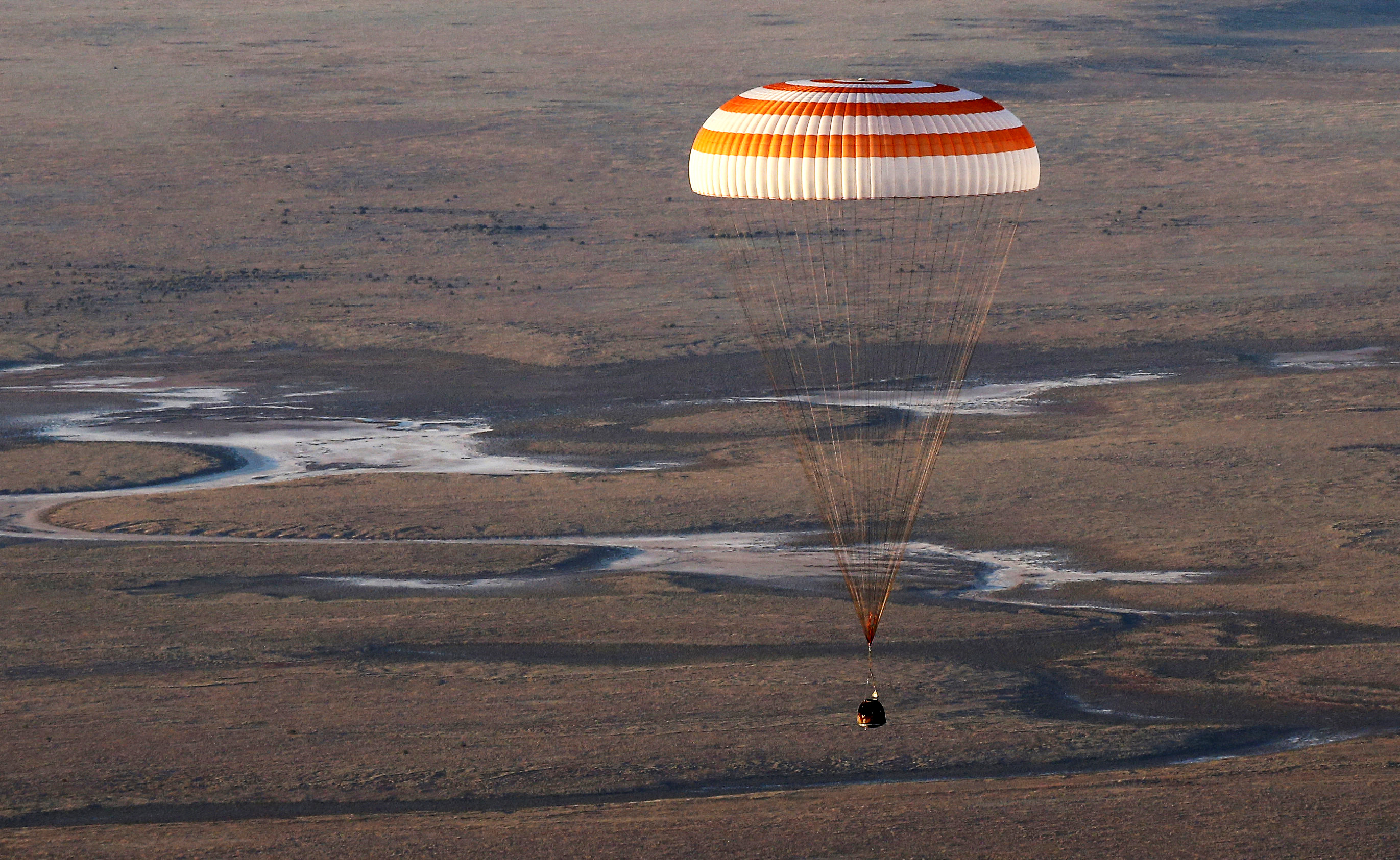 The Soyuz TMA-20M spacecraft capsule carrying International Space Station (ISS) crew descends beneath a parachute near the town of Zhezkazgan (Dzhezkazgan), Kazakhstan
