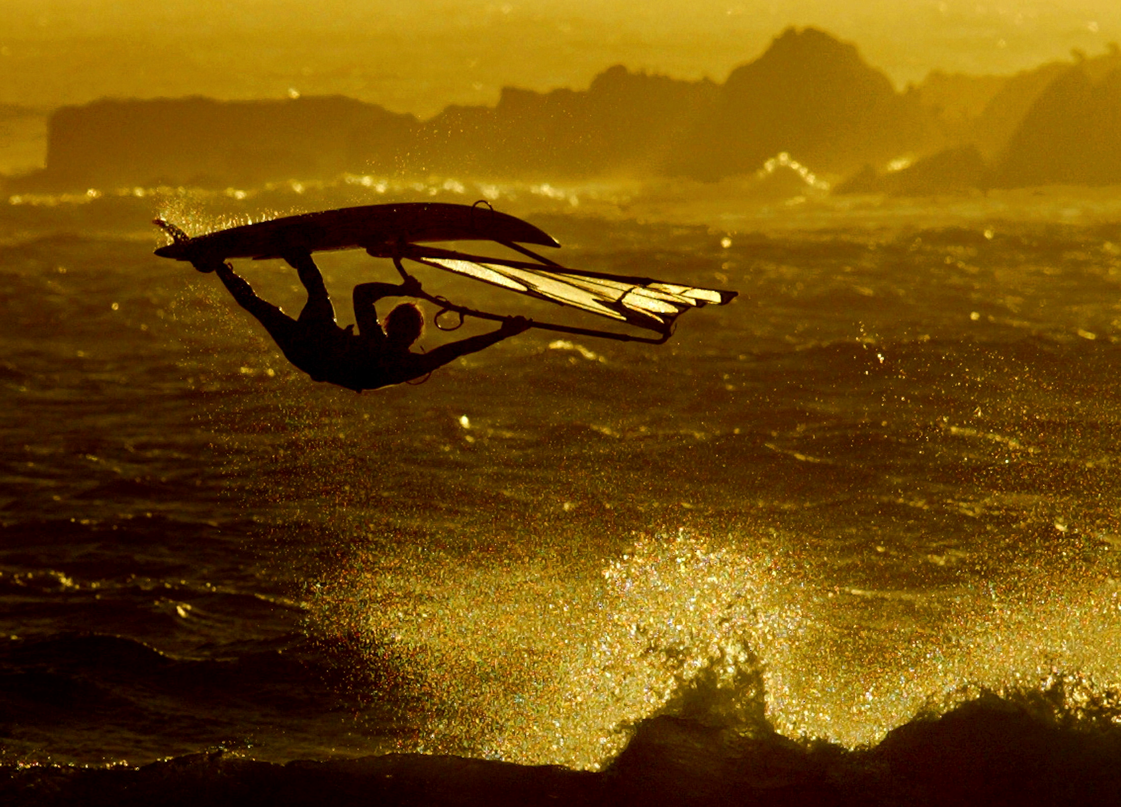 A windsurfer gets airborne as the sun sets over Cape Town's Blaauwberg beach, February 23, 2004.