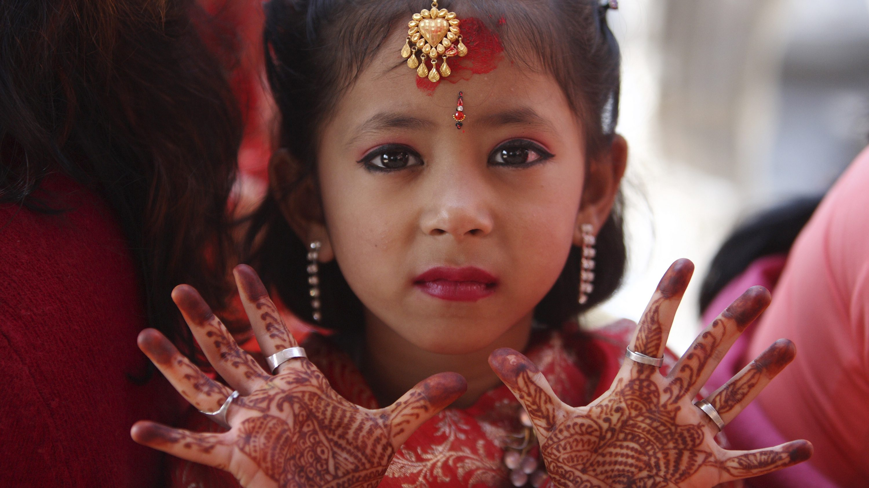 "A Newar girl shows her palms decorated with henna to the camera during an Ihi ceremony in Kathmandu November 20, 2009. Girls aged odd years before puberty are married to Bel, the fruit of an wood-apple tree in the ceremony. Ihi is a two-day ceremony which begins with purification rituals and ends with ""Kanyadan"" (giving away the virgin) of the girl by her father. In this way, a Newar girl is married thrice in her life first with a wood apple tree fruit. A second time with the sun and finally with a human later in life. REUTERS/Gopal Chitrakar (NEPAL SOCIETY IMAGES OF THE DAY) - RTXQY6K"
