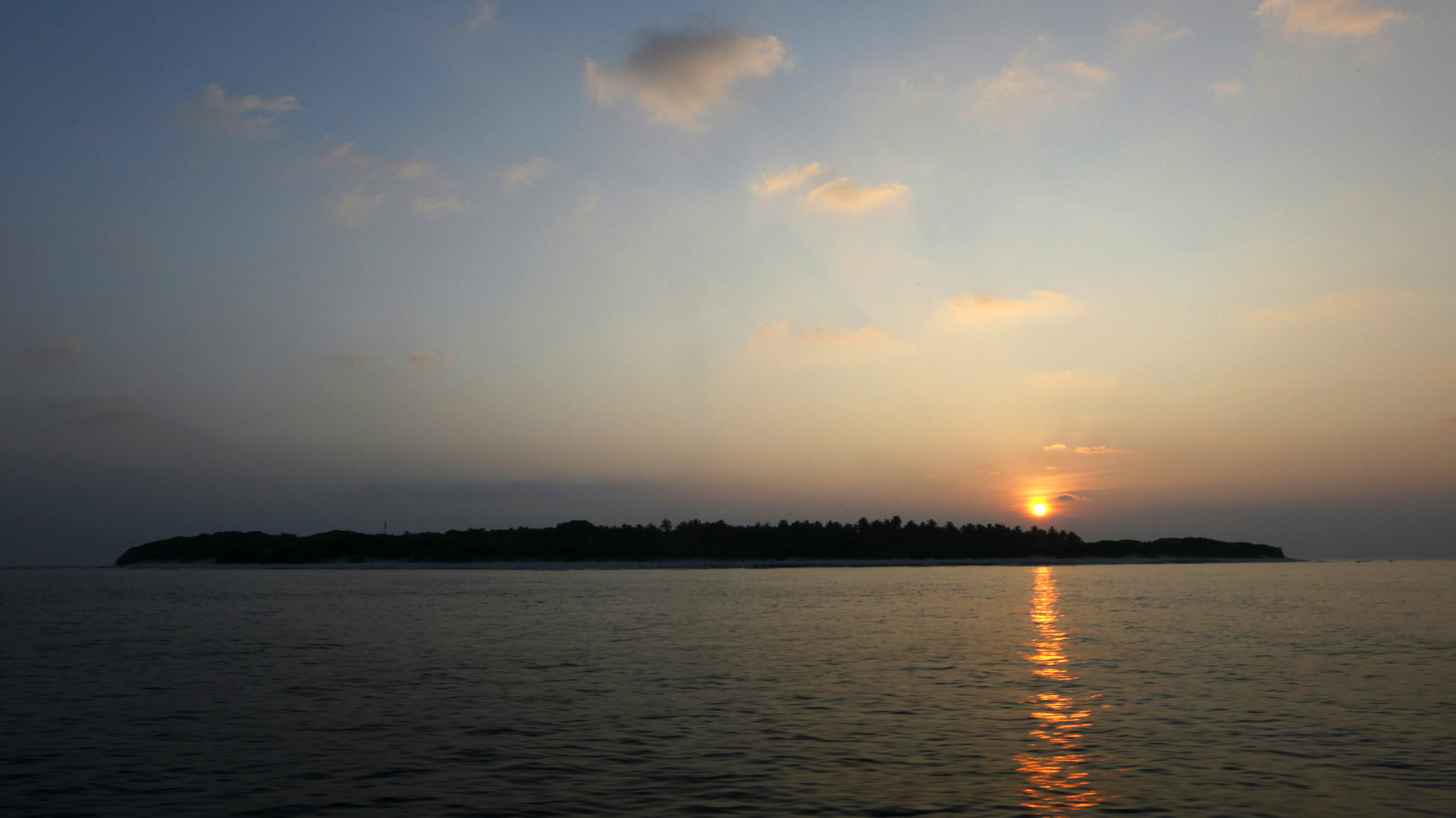 The sun rises over an island at Har Alif Atoll December 12, 2009