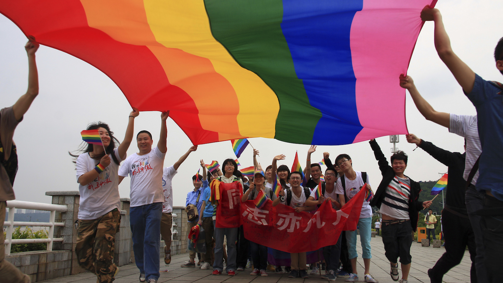 "Gay-rights activists in the Hunan province hold a banner that reads ""Homosexsuals are also ordinary people""."
