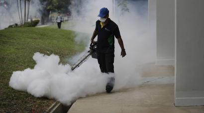 A pest control worker fumigates in Singapore to fight Zika