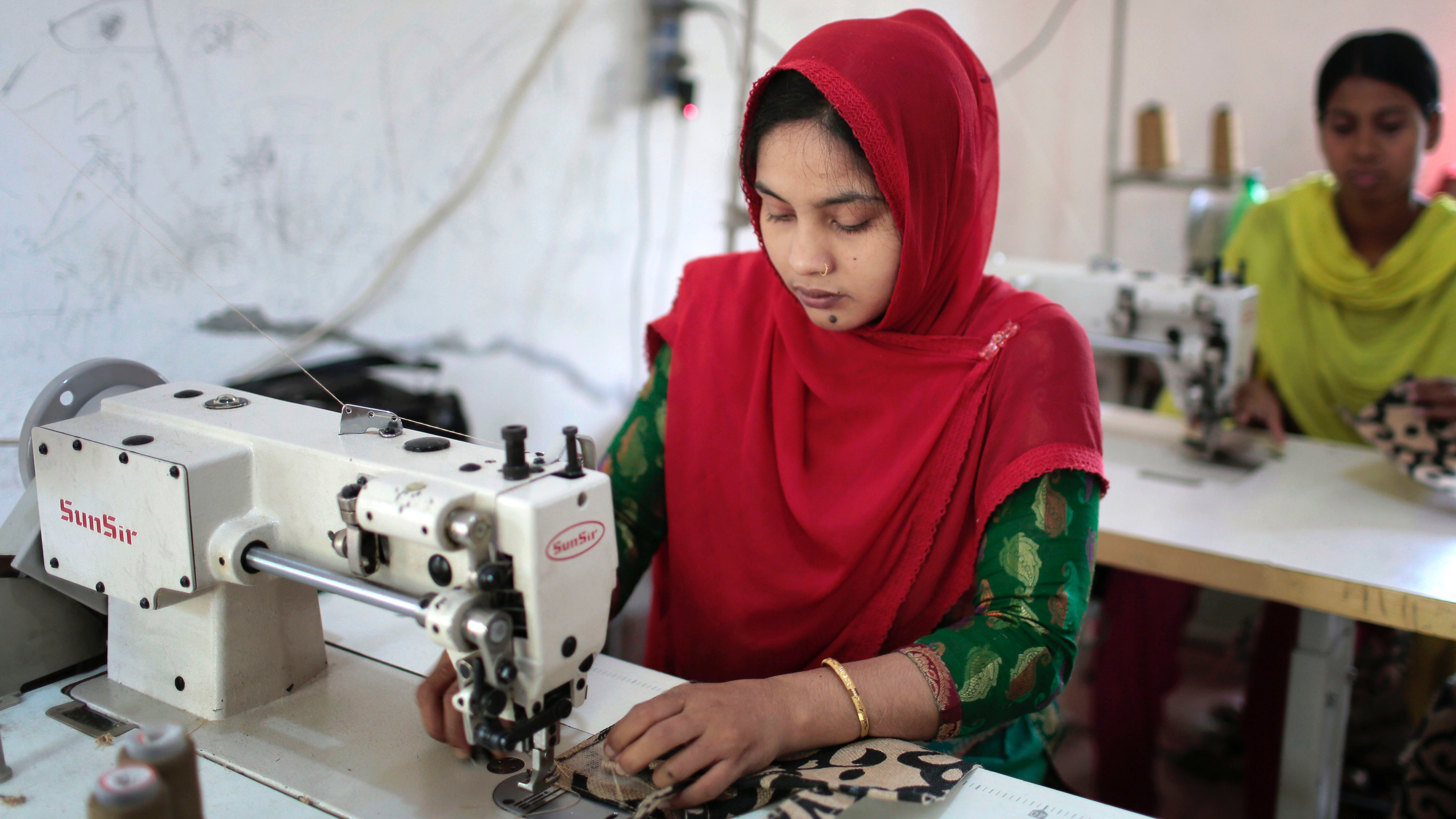 FILE- In this April 20, 2015 file photo, Bangladeshi garment workers, who worked at the Rana Plaza garment factory that collapsed two years ago, work at a factory meant to rehabilitate survivors of the accident, the worst in the history of the garment industry, in Savar, near Dhaka, Bangladesh. The bloody weekend attack by Bangladeshi militants that left more than two dozen dead has also dealt a deadly blow to the country's vital garment industry. Clothing manufacturing, the Southeast Asian nation's top export industry, had been recovering after a disastrous factory collapse three years ago shook up the industry, forcing workshops producing for foreign brands to improve working conditions. (AP Photo/A.M. Ahad, File)