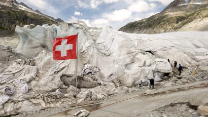 White canvas covers protect parts of the Rhone glacier against melting as visitors enter an ice cave near the Furka mountain pass at 2429 metres (7969 ft) altitude in the Swiss Alps, Switzerland August 6, 2015. Switzerland's national flag is pictured in the foreground. REUTERS/Arnd Wiegmann/File Photo - RTSJ10I