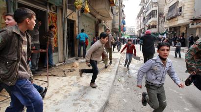 People run upon hearing a nearby plane bombing during a protest against Syrian President al-Assad in Aleppo