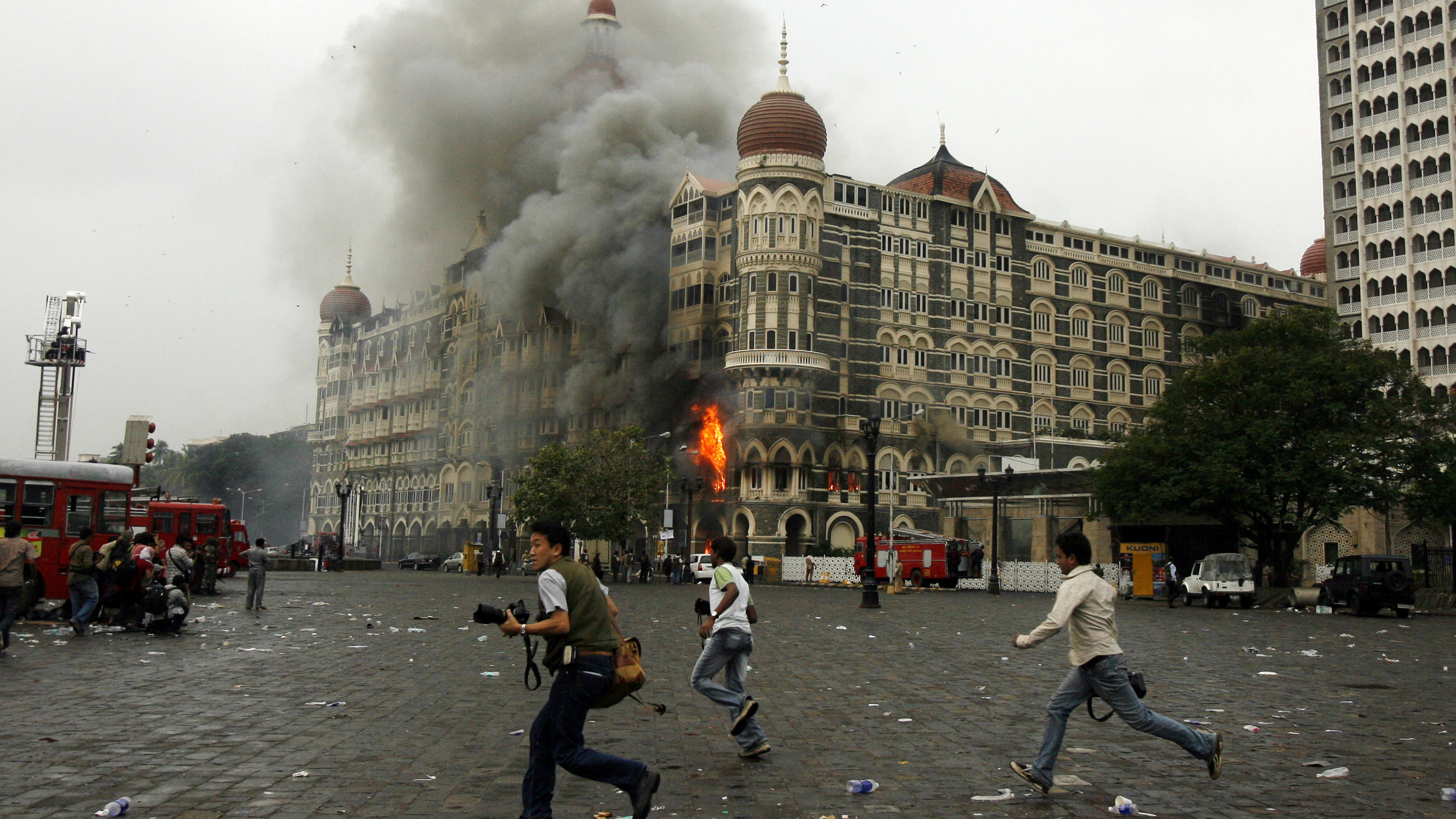 Photographers run past burning Taj Mahal Hotel during a gun battle in Mumbai November 29, 2008. Operations by Indian commandos to dislodge Islamist militants at Mumbai's Taj Mahal hotel ended on Saturday, Indian television channels quoted officials as saying. The hotel came under heavy gunfire and flames leaped out of the building shortly before the announcement. REUTERS/Arko Datta (INDIA)