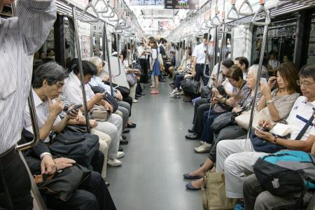Everyone is on their smartphones in the subway in Japan.