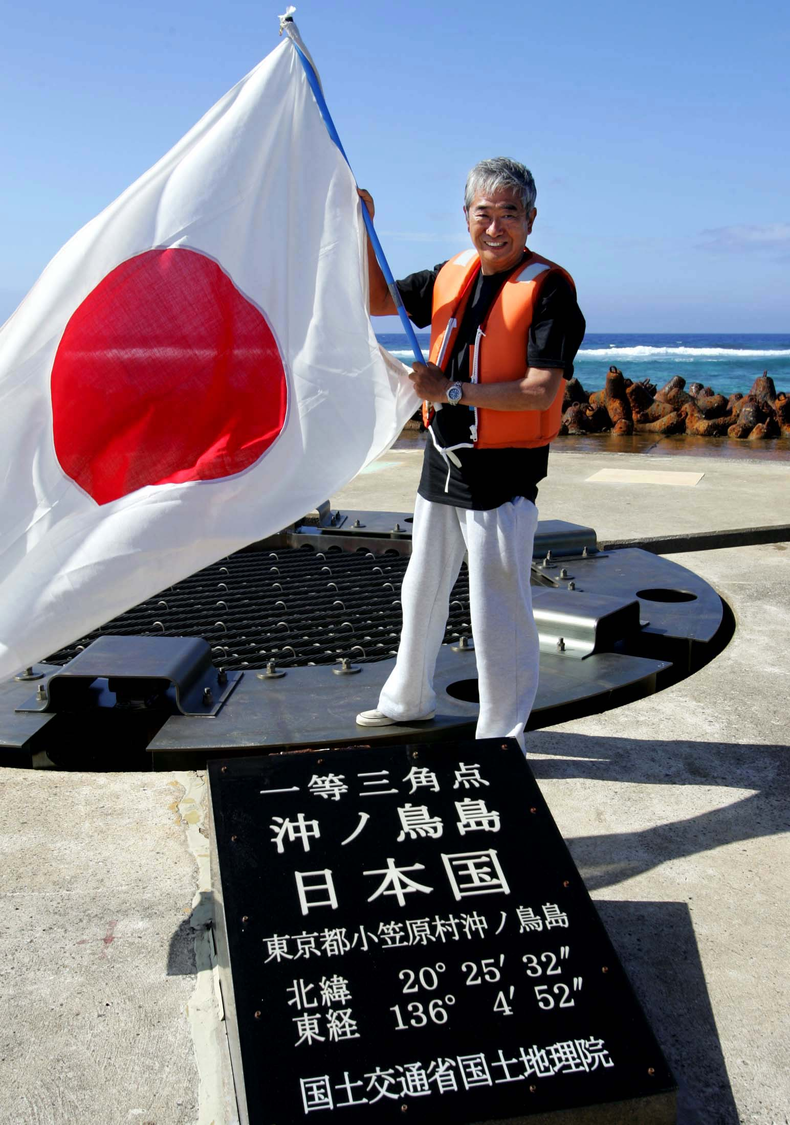 Tokyo Governor Shintaro Ishihara waves the Japanese national flag as he inspects Okinotorishima.