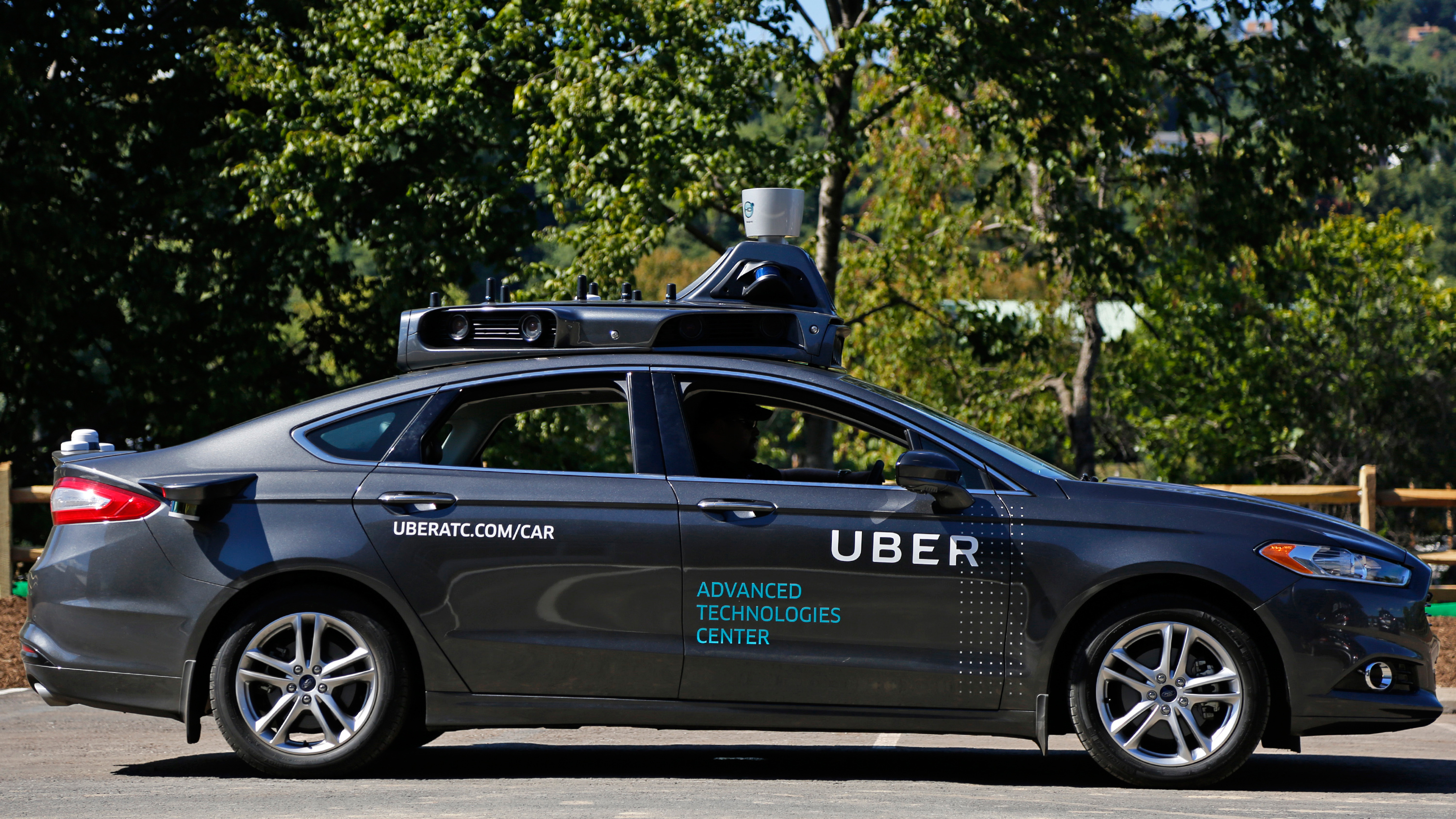 Uber safety driver Zachary Rearick sits in a self driving Uber after taking journalists on a ride through the streets of downtown Pittsburgh, Monday, Sept. 12, 2016. Starting Wednesday morning, Sept. 14, 2016 dozens of self-driving Ford Fusions will pick up riders who opted into a test program with Uber. While the vehicles are loaded with features that allow them to navigate on their own, an Uber engineer will sit in the driver's seat and seize control if things go awry. (AP Photo/Gene J. Puskar)