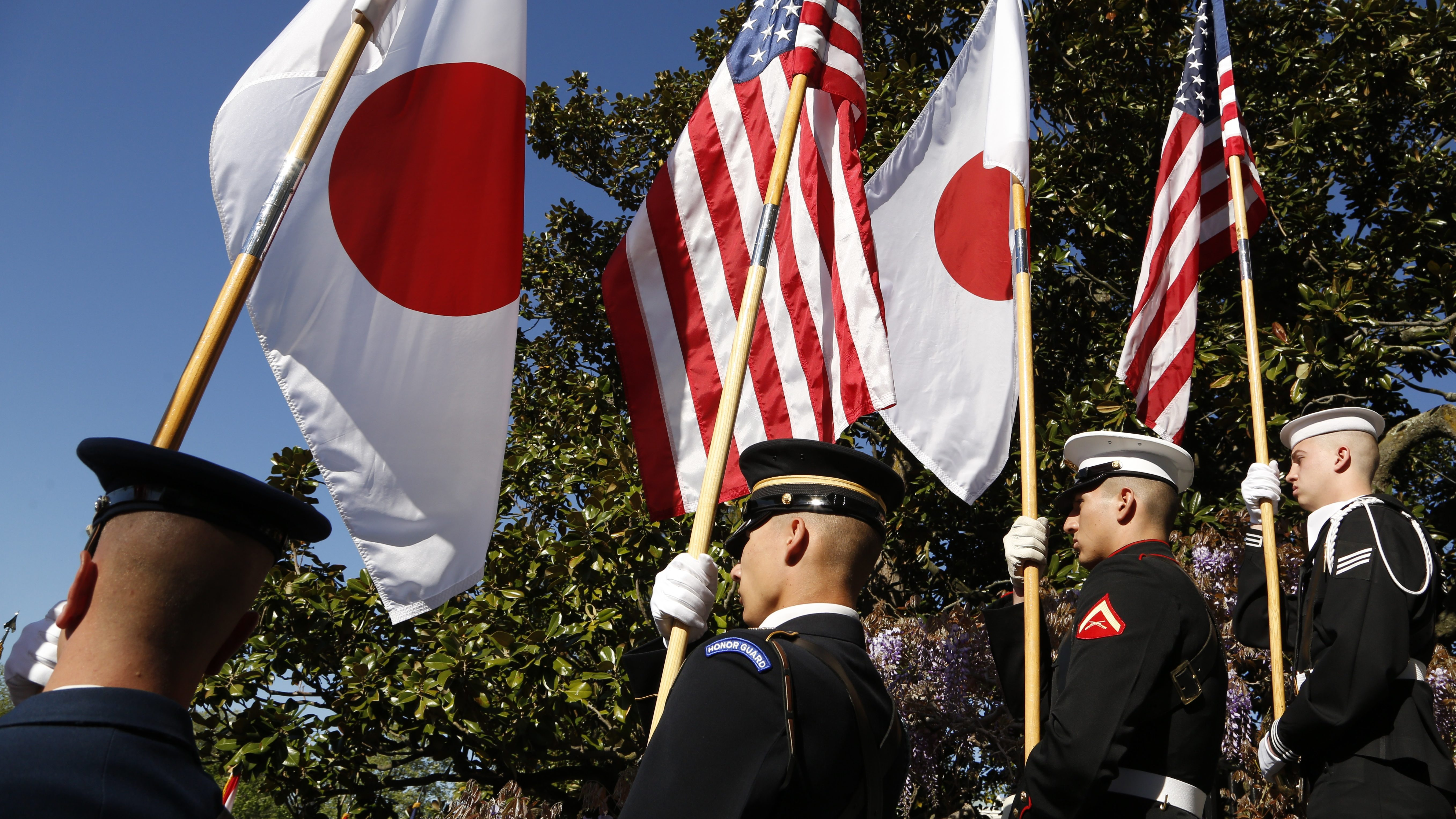 An honor guard carries U.S. and Japanese flags during an official arrival ceremony for Japanese Prime Minister Shinzo Abe on the White House South Lawn in Washington, April 28, 2015.