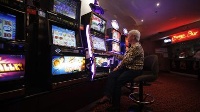 An elderly woman sits in front of a slot machine