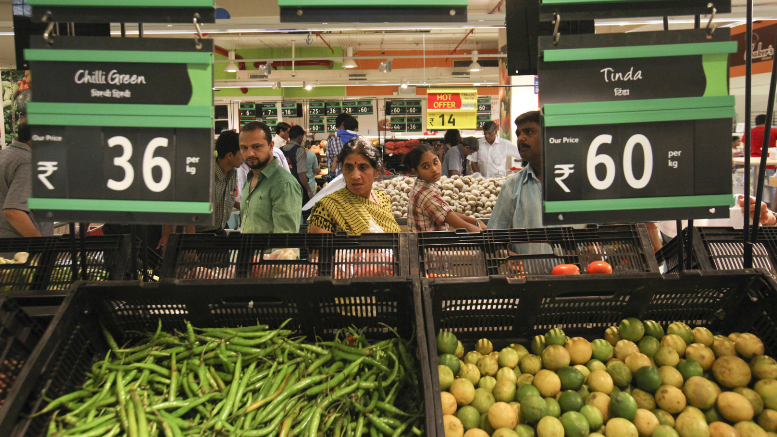Prices for various vegetables are displayed as people shop in the fresh foods section of a Reliance Fresh supermarket in Mumbai October 16, 2011. Five years after making a grand foray into retail, Mukesh Ambani's Reliance Industries is nowhere close to the scale he had hoped his company, India's largest listed group, would achieve in a fragmented and fast-growing industry. With retail giants Wal-Mart Stores Inc and Carrefour circling India in anticipation of a rule change that would allow foreign investment in supermarkets, Asia's richest man is scrambling to capitalise on his early mover advantage.