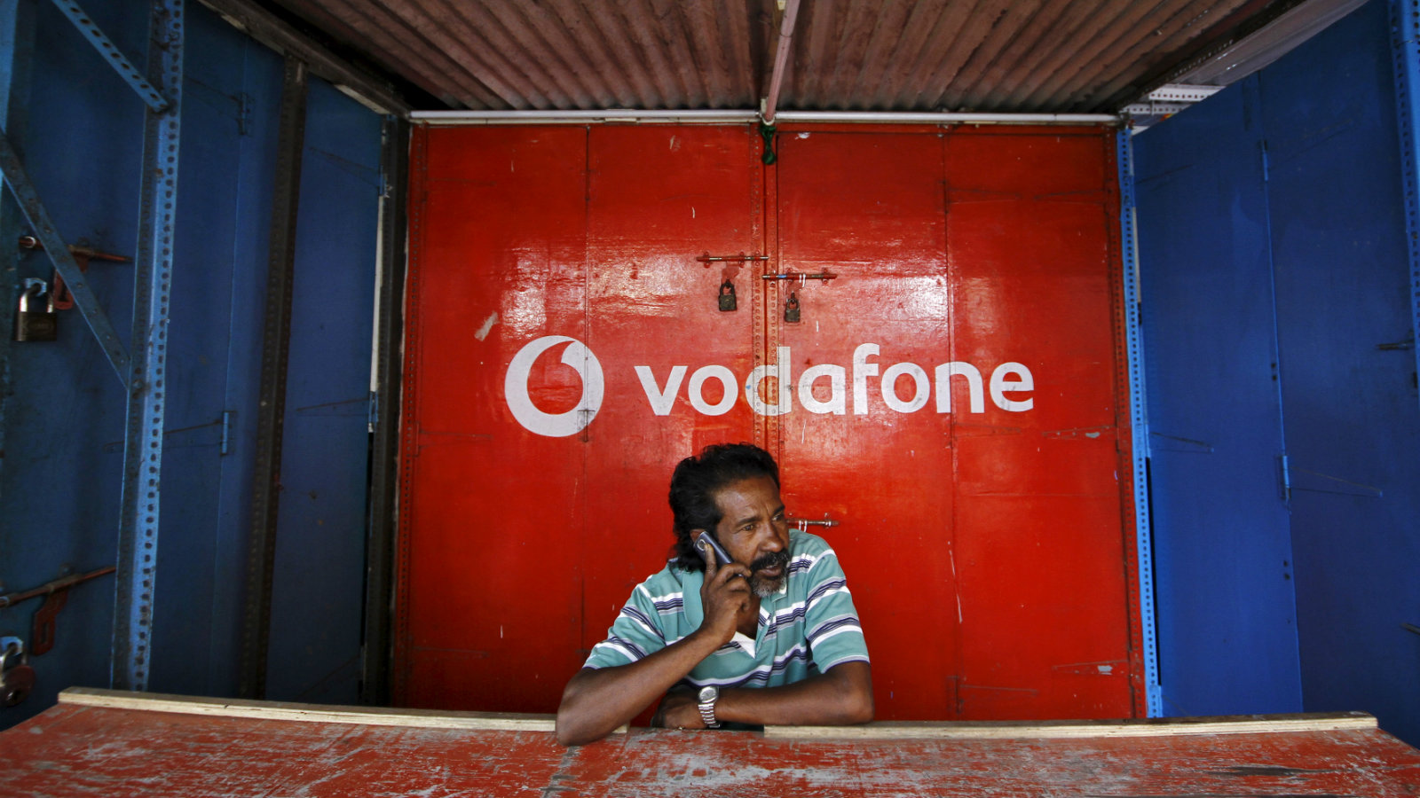 A retail shop owner speaks on his mobile phone outside his closed shop shutters painted with an advertisement for Vodafone at a market in the southern Indian city of Chennai December 30, 2013.