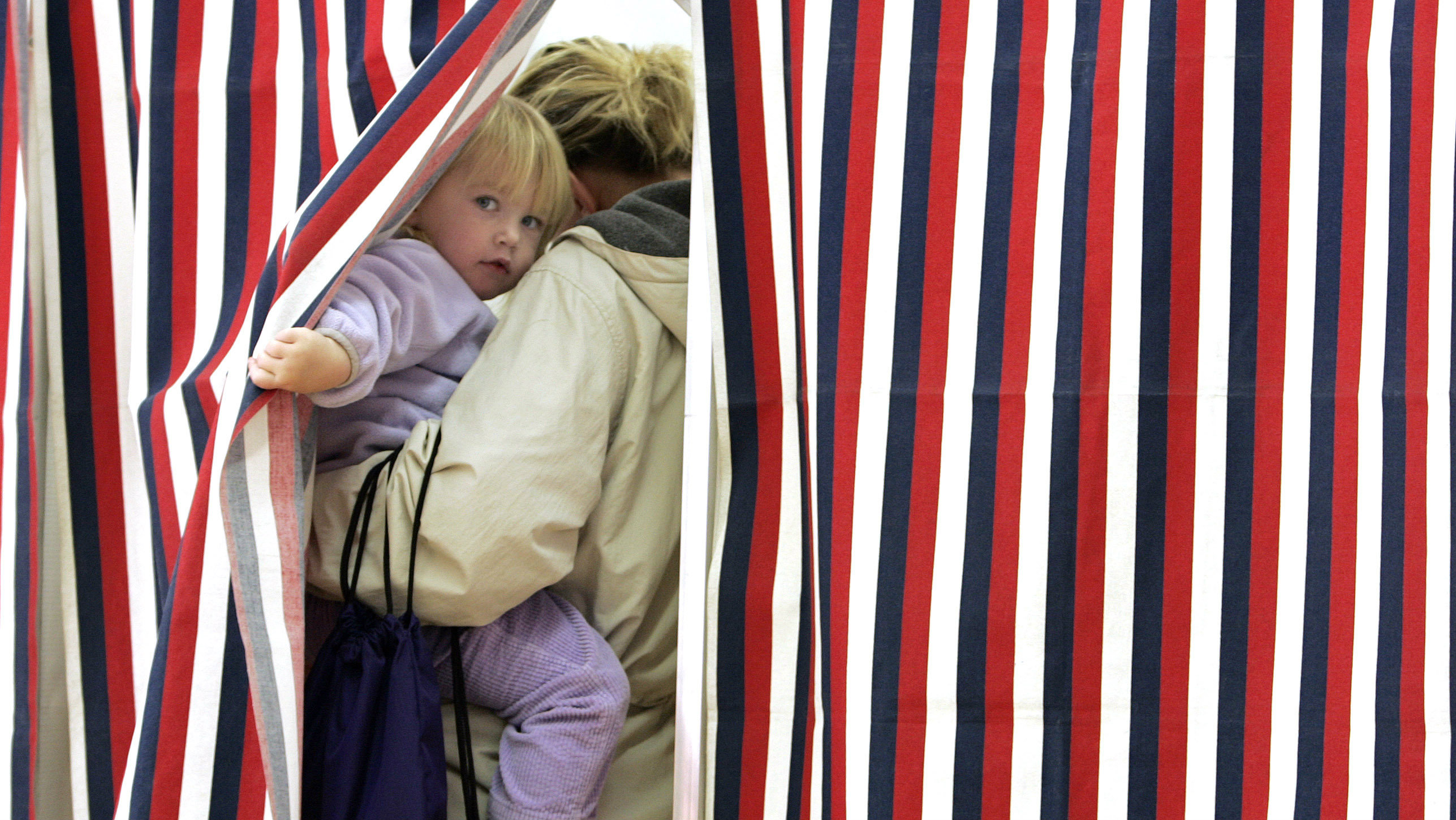 Elyse Holmes, 2, peaks out as her mother Helen Holmes votes at Madbury Town Hall in Madbury, New Hampshire November 4, 2008. REUTERS/Adam Hunger (UNITED STATES) US PRESIDENTIAL ELECTION CAMPAIGN 2008 (USA)