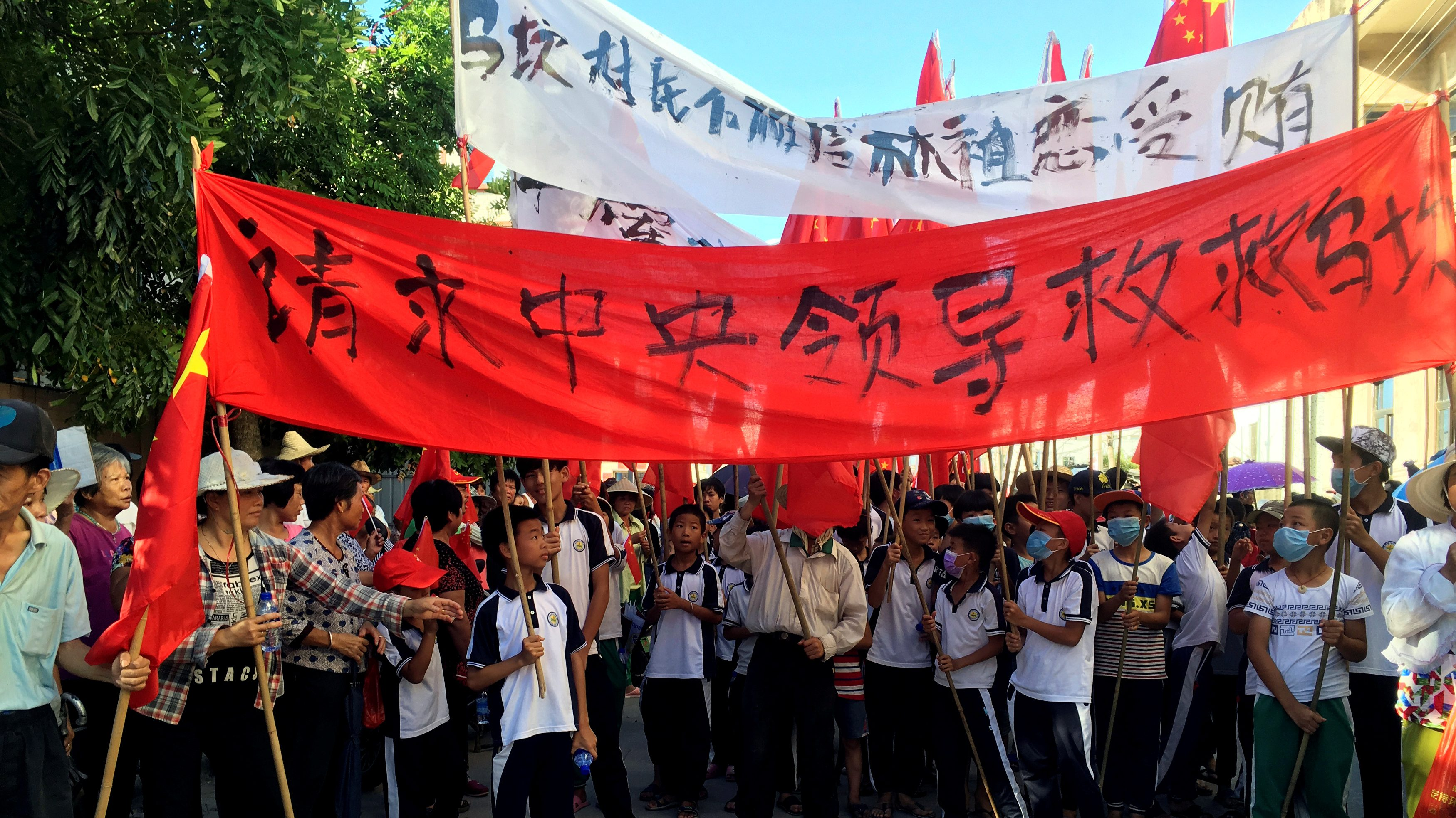 """Villagers carry banners which read """"Plead the central government to help Wukan"""" (in red) and """"Wukan villagers don't believe Lin Zuluan took bribes"""" during a protest in Wukan, China's Guangdong province June 22, 2016."""