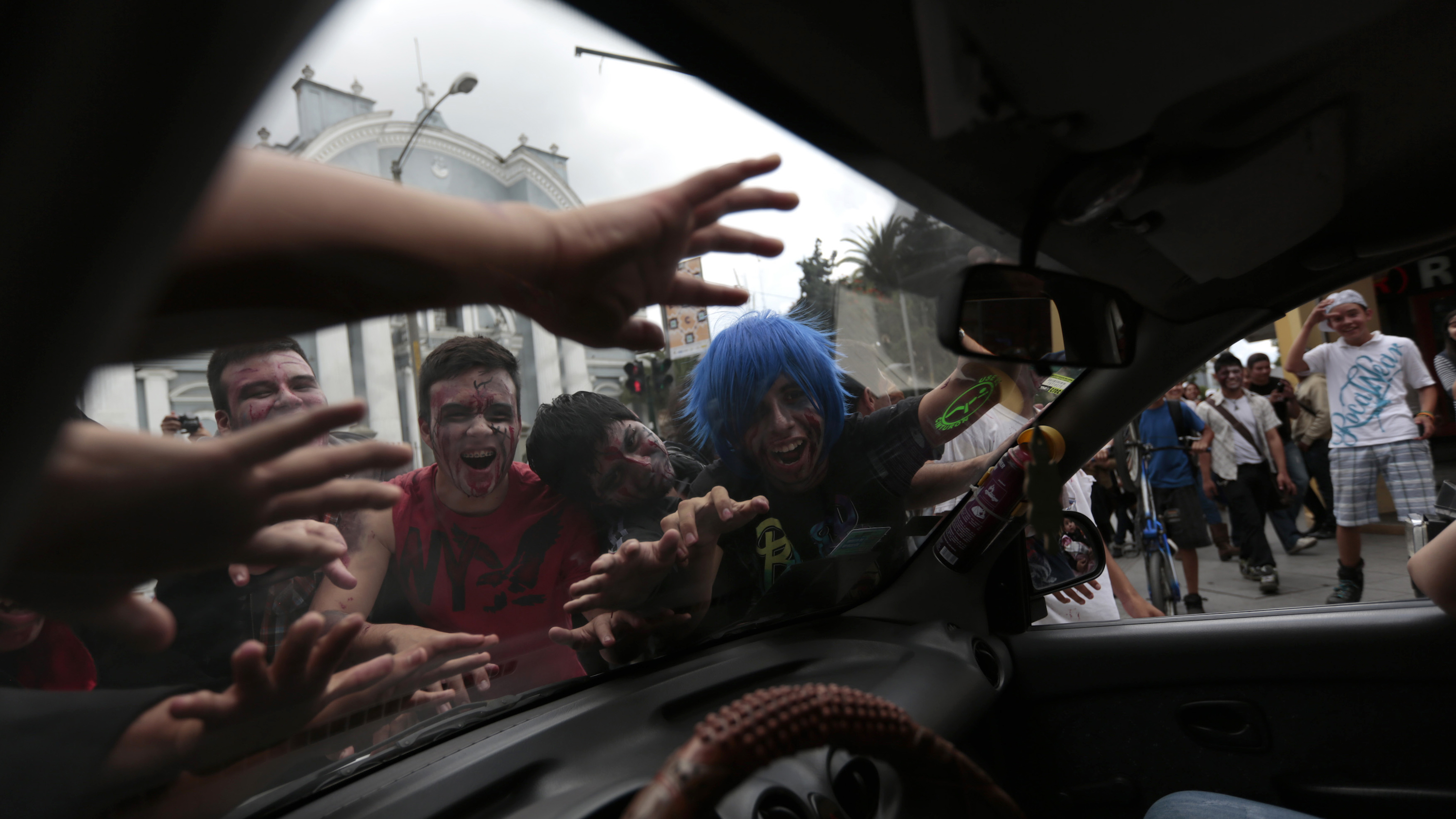 People dressed as zombies crowd a car during a Zombie Walk on the streets of Guatemala City