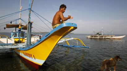 A Filipino fisherman sits on the hull of his boat after arriving from Scarborough Shoal