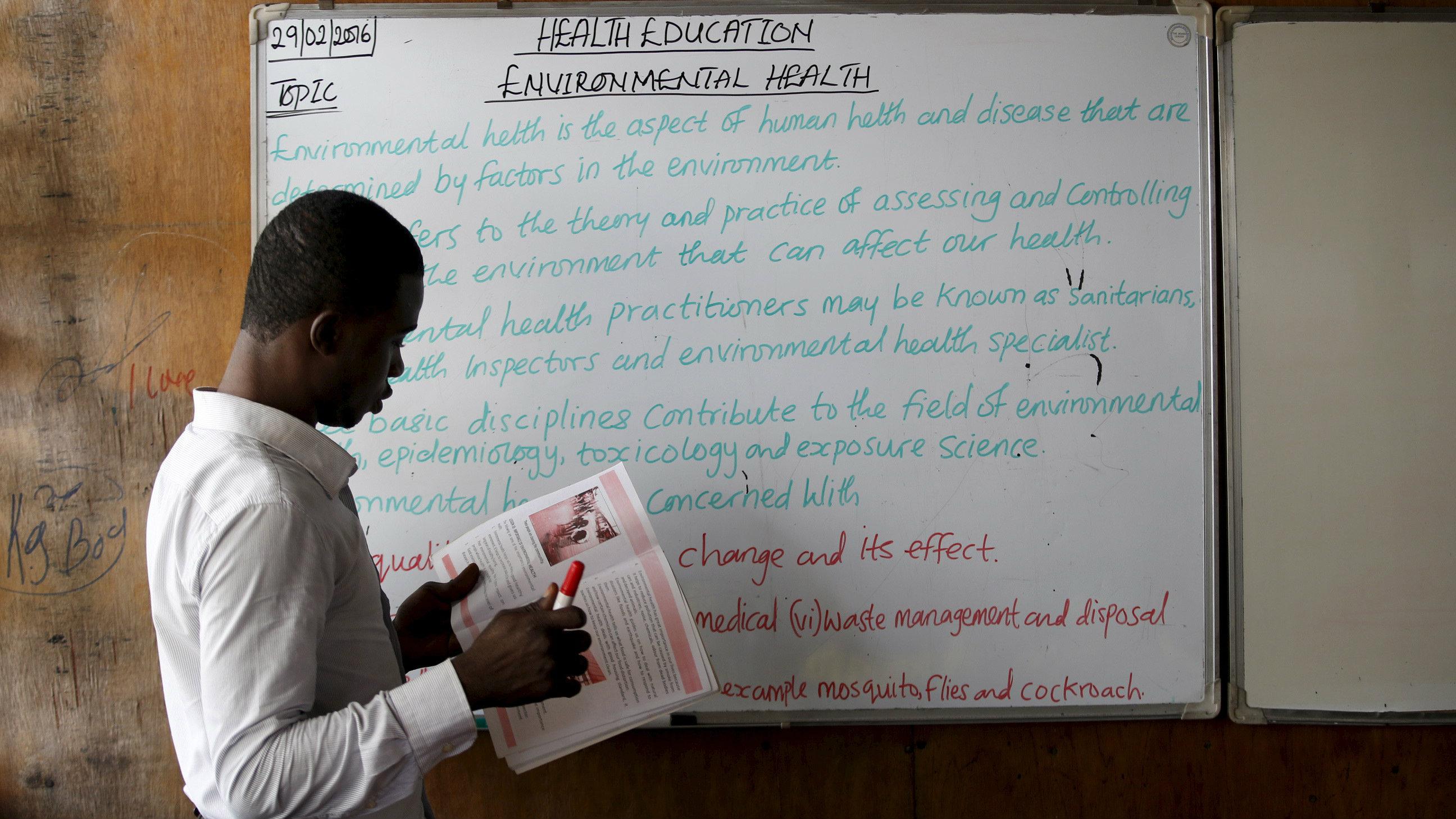 A teacher writes on the board at a floating school in Makoko fishing community on Lagos Lagoon, Nigeria February 29, 2016.