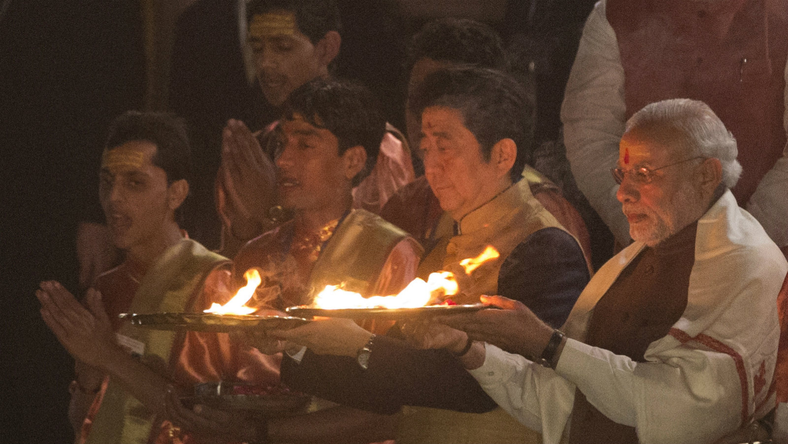 Japanese Prime Minister Shinzo Abe, second right, and Indian Prime Minister Narendra Modi, right, attend the Ganga aarti, a religious ceremony or a prayer for the river Ganges, in Varanasi, India, Saturday, Dec. 12, 2015. India and Japan have signed agreements on military purchases for India's armed forces, high-speed trains and upgrading India's infrastructure.