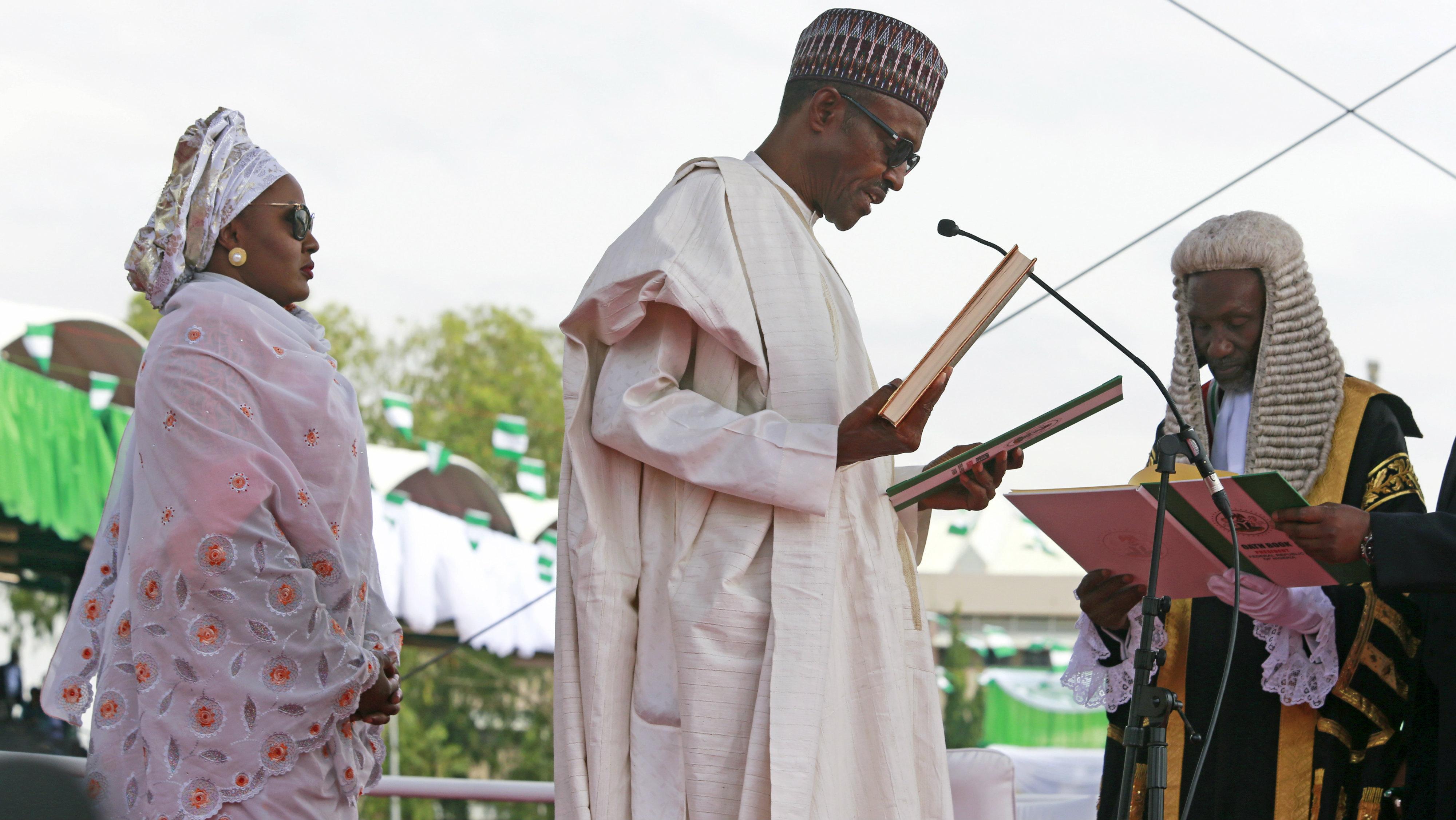 Chief Justice of Nigeria Mahmud Mohammed swears in Muhammadu Buhari (C) as Nigeria's president while Buhari's wife Aisha looks on at Eagle Square in Abuja, Nigeria May 29, 2015.