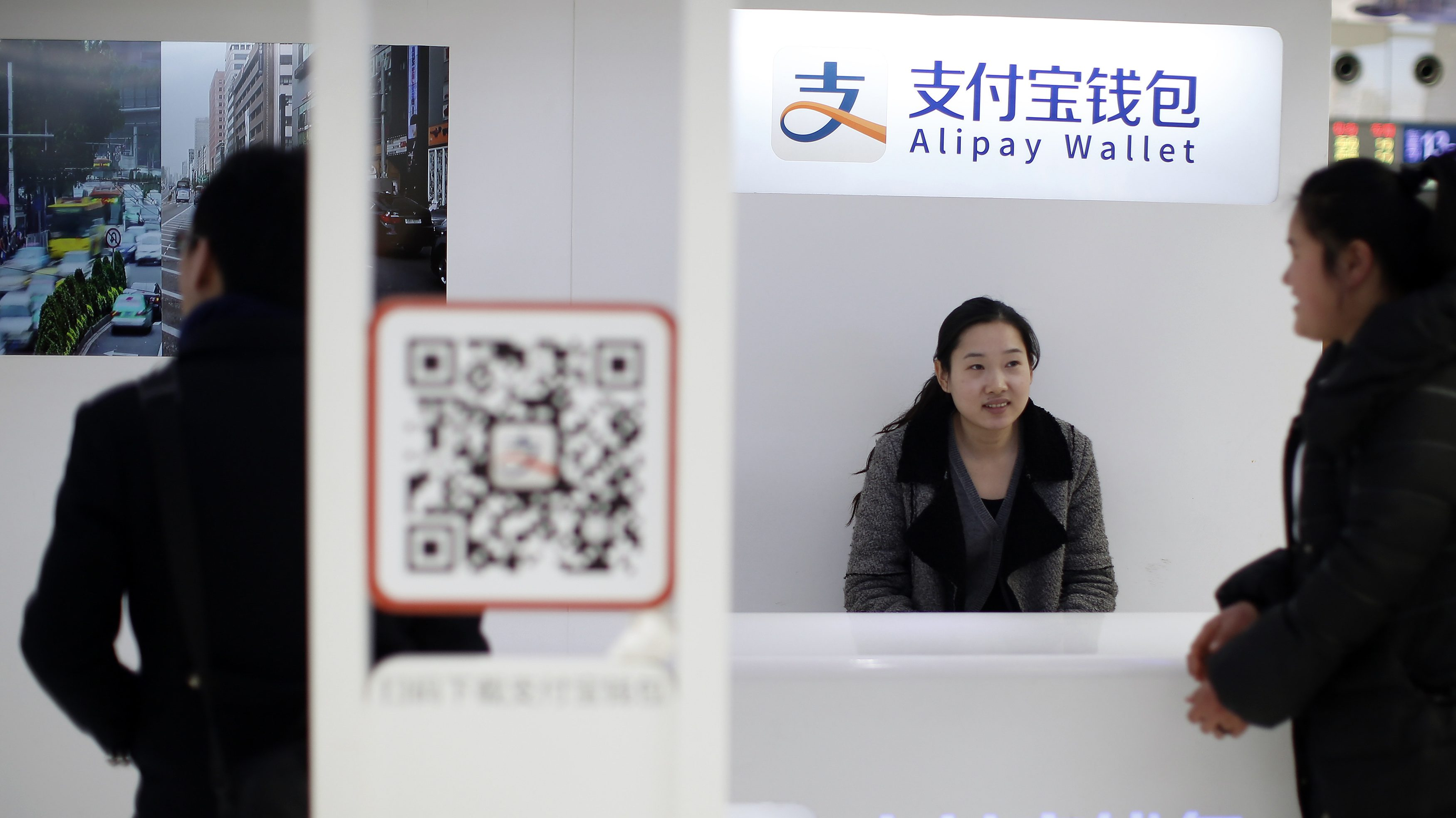 "A sales assistant sits behind and under Alipay logos at a train station in Shanghai, February 9, 2015. Ant Financial Services Group, an affiliate of Chinese e-commerce titan Alibaba, is in negotiations for funding that have reached a ""critical stage"" and value the company at $30 billion, news magazine Caixin reported on Monday. Ant Financial runs Alipay, China's most widely used online payment platform which is seen as a crucial part of Alibaba's business."