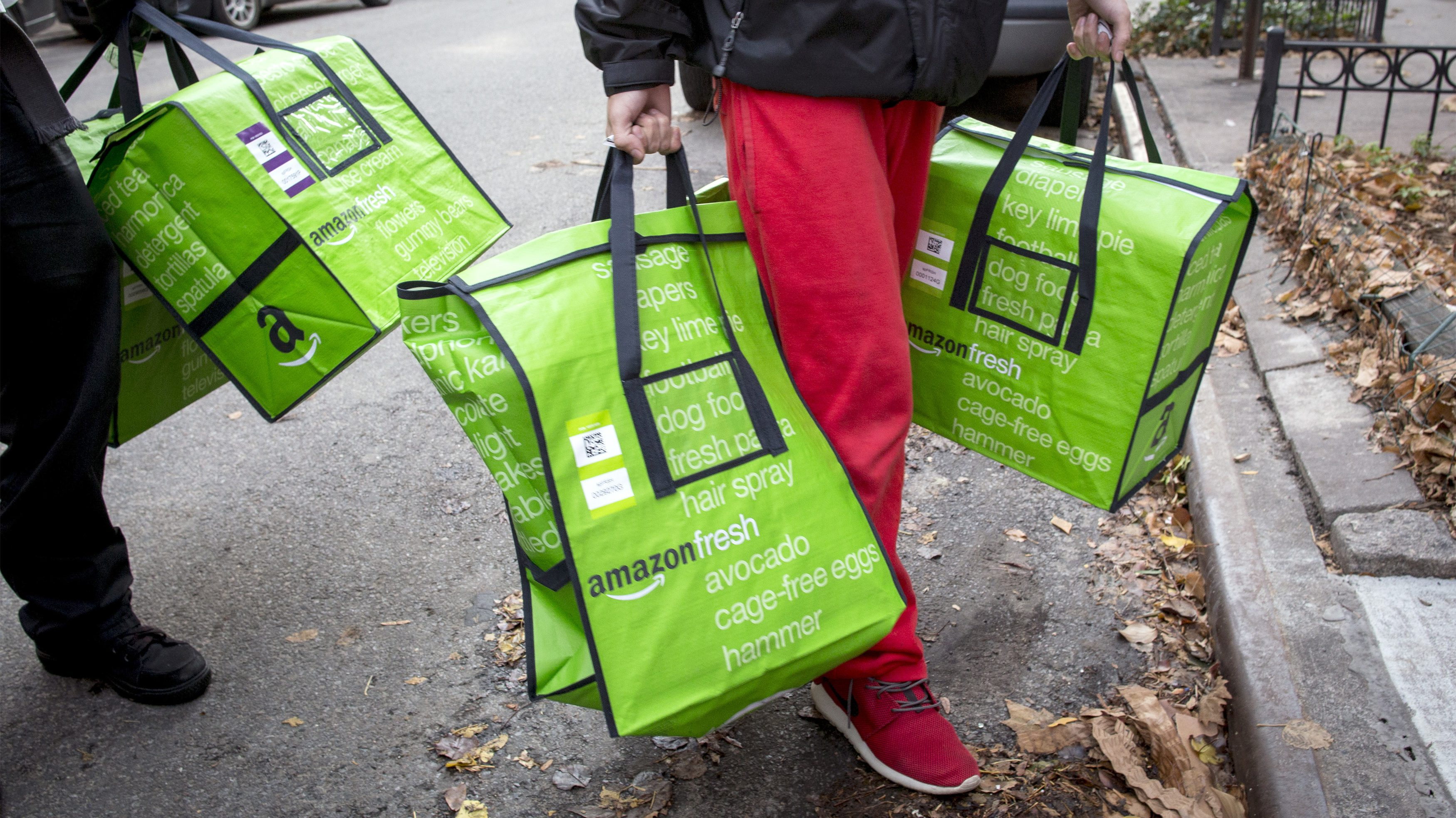 Amazon workers deliver groceries from the Amazon Fresh service in Brooklyn.