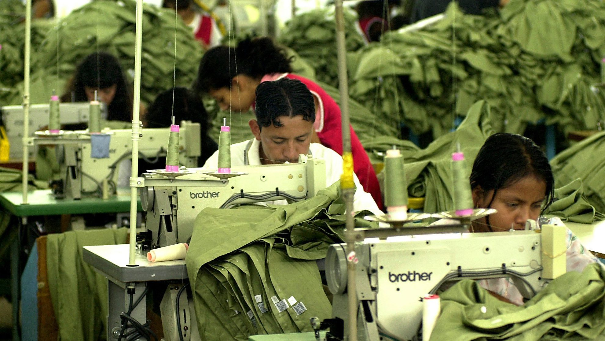 Workers sew at a maquila, or sweatshop, in Guatemala City, Guatemala on Tuesday, Oct. 2, 2001. Central American sweatshops have an uncertain future due to the Sept. 11 attacks on the United States, which could affect the exportation of goods (AP Photo/Jaime Puebla)