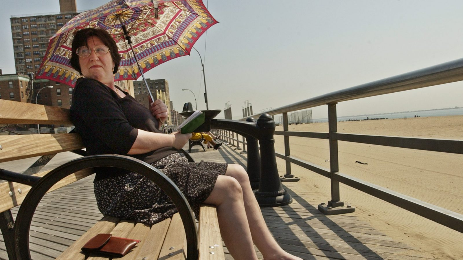 Russian immigrant, who only identified herself as, Zenaida, uses an umbrella to shield herself from the midday sun as she studies her English on the boardwalk at Coney Island, Tuesday, April 16, 2002, in New York. Record high temperatures blanketed the metropolitan New York area Tuesday. (AP Photo/Kathy Willens)