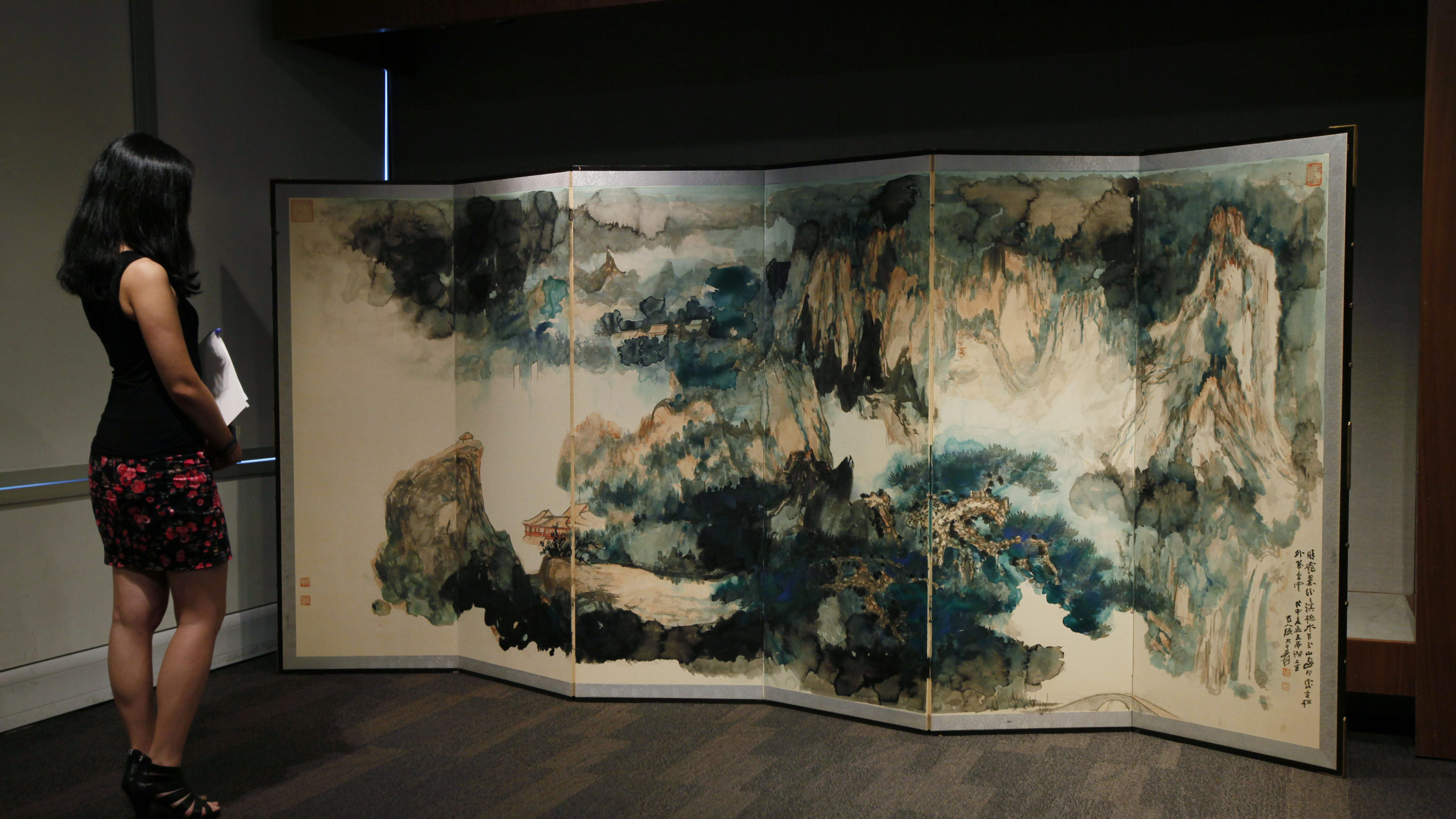 """A staff member looks at the painting """"Recluse in the Summer Mountains"""" by Chinese artist Zhang Daqian during a Sotheby's exhibition preview in Hong Kong Wednesday, Sept. 14, 2011. The six-panel screen was given to his daughter by Zhang Daqian as a wedding gift. The painting will be shown on public from Oct. 1 to 5, 2011. (AP Photo/Kin Cheung)"""