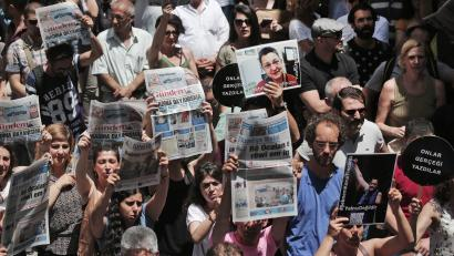 Protesters demonstrate against the jailing of two journalists and an academic, outside the offices of Ozgur Gundem in Istanbul, Turkey