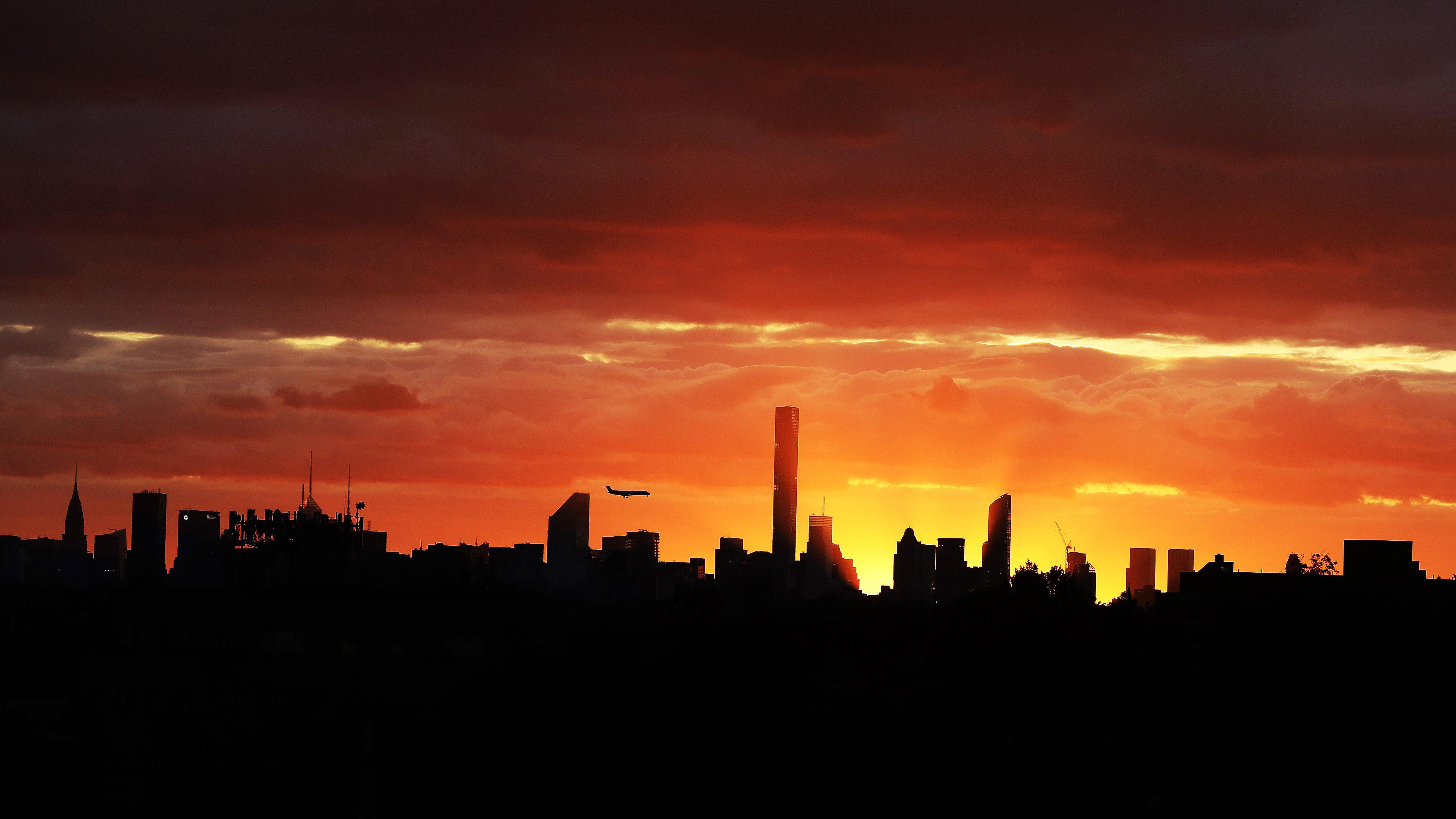 A plane flies near the Manhattan skyline at sunset, as seen from the USTA Billie Jean King National Tennis Center during the U.S. Open tennis tournament, Tuesday, Sept. 6, 2016, in New York. (AP Photo/Darron Cummings)