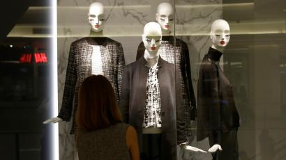 A woman watch in front of a display of mannequins wearing black and white clothing at a shopping mall in Bangkok, Thailand, Monday, Oct. 17, 2016. Authorities are urging calm as social media throbs with criticism of people who aren't wearing black and white clothing to mourn the revered monarch and some arch-royalists take to reprimanding people in public. (AP Photo/Sakchai Lalit)
