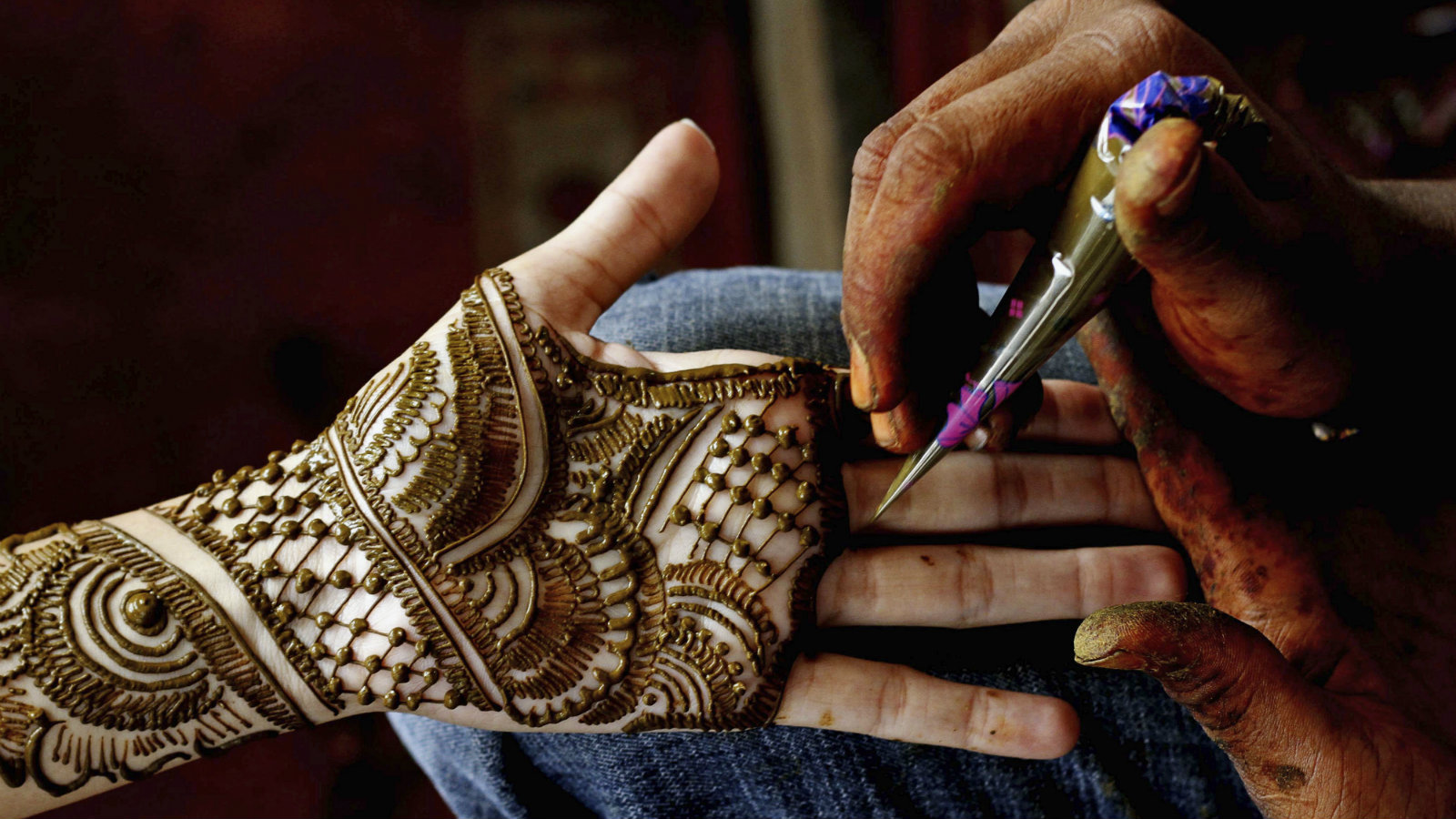 An Indian woman get henna designs applied on her palm during the Hindu festival of Karva Chauth in the eastern Indian city Bhubaneswar, India, Friday, Oct. 30, 2015. Hindu married women decorate their hands with henna, wear colorful bangles and observe a fast to pray for the longevity and well being of their husbands during this festival.