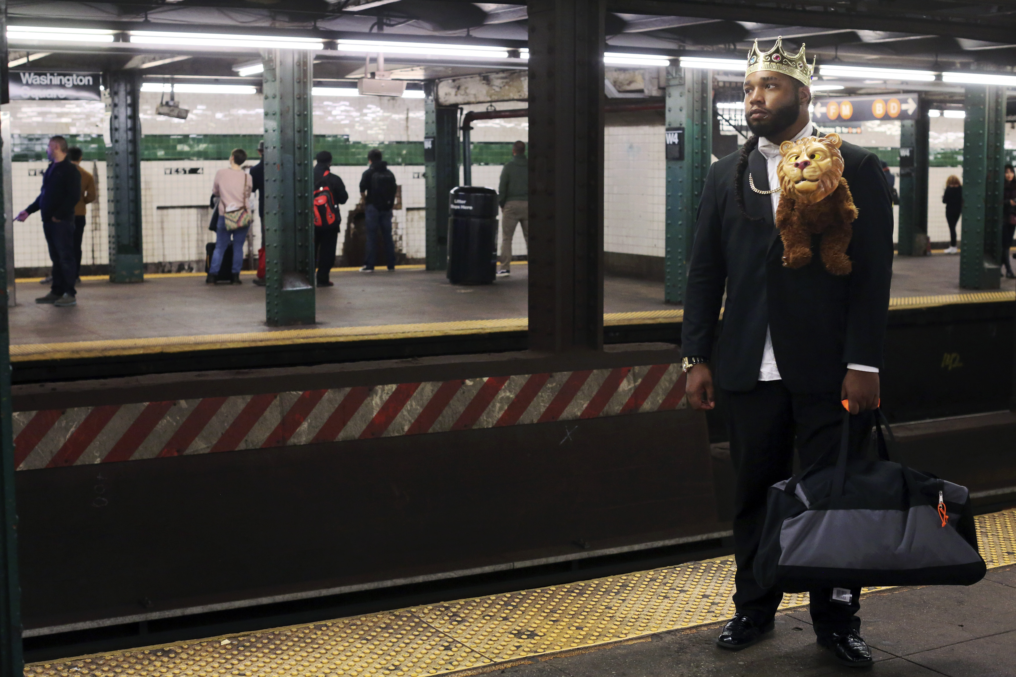 """Ro'zaye Bellevue, dressed as Prince Akeem from the movie """"Coming to America"""" for Halloween, waits for the train at the West 4 Street Station, Saturday, Oct. 31, 2015, in New York."""