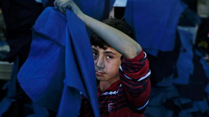 In this Thursday, June 2, 2016 photo, Mohammed, a Syrian refugee child works at a clothing workshop in Gaziantep, southeastern Turkey. According to the United Nation's Children's Fund, or UNICEF, more than half of Turkey's 2.7 million Syrian refugees are children. Only 325,000 of them are enrolled to school. About half a million of school-aged children have no access to education. (AP Photo/Lefteris Pitarakis)