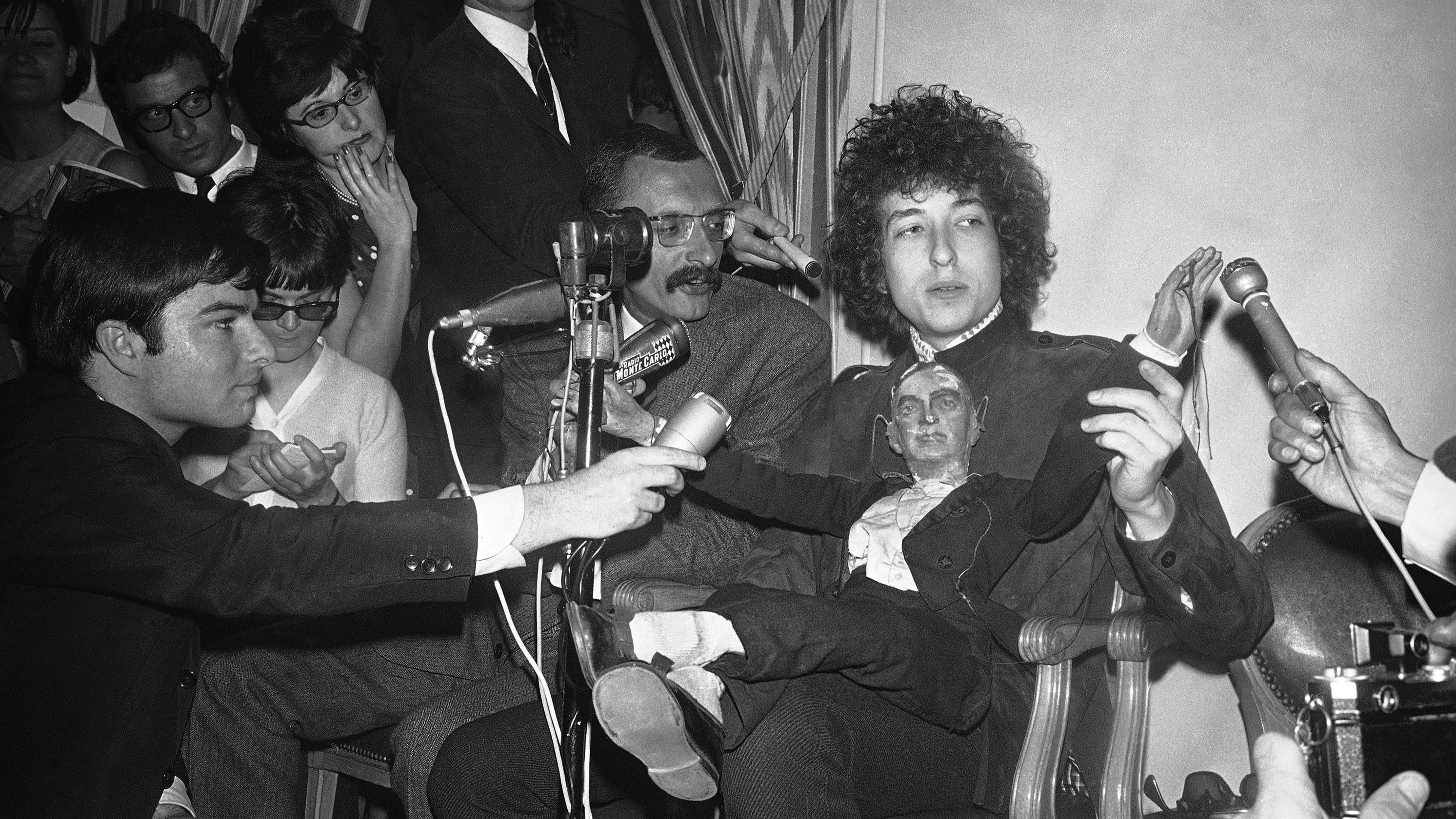 American folk singer Bob Dylan sits with a puppet as he faces the media during a press conference at the Hotel George V in Paris, France on May 23, 1966. He will appear on Tuesday at the Paris Olympia music-hall. (AP Photo/Pierre Godot)