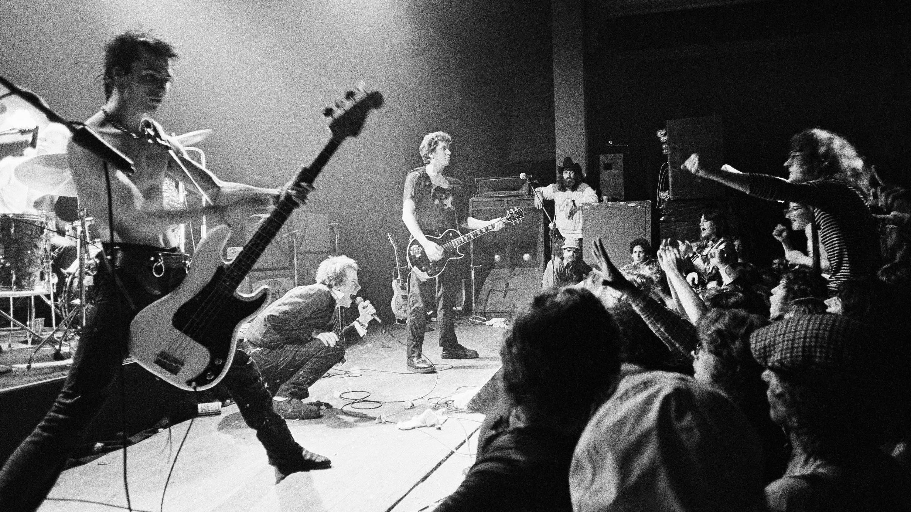 """English punk rock group """"Sex Pistols"""" get a form of audience participation on January 7, 1978 in Memphis, Tenn., during the second stop of their American tour. In left foreground is bass player Sid Vicious while group leader Johnny Rotten crouches in foreground."""