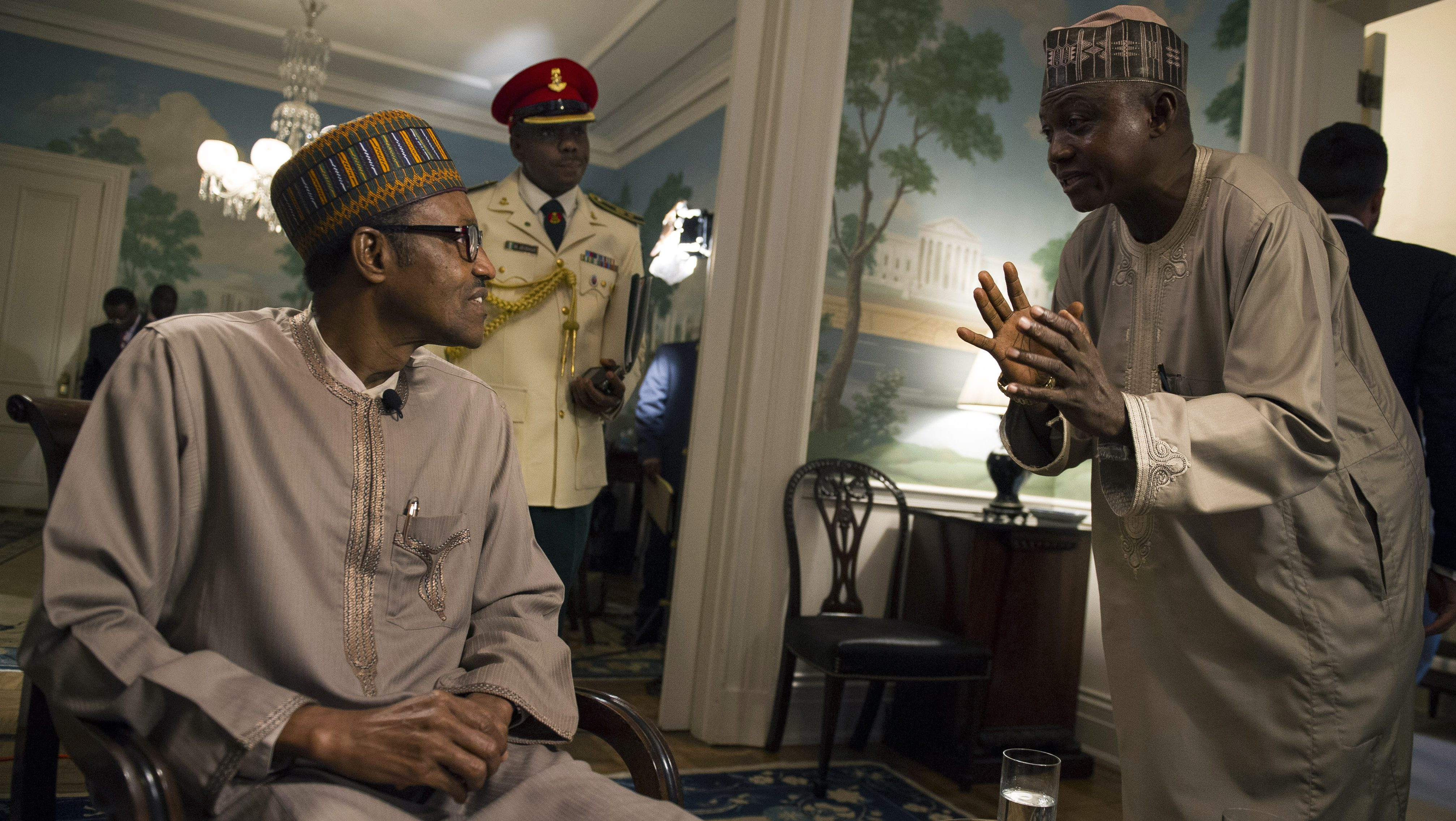 Nigerian President Muhammadu Buhari confers with advisor between news media interviews at Blair House in Washington, Tuesday, July 21, 2015. (AP Photo/Cliff Owen)